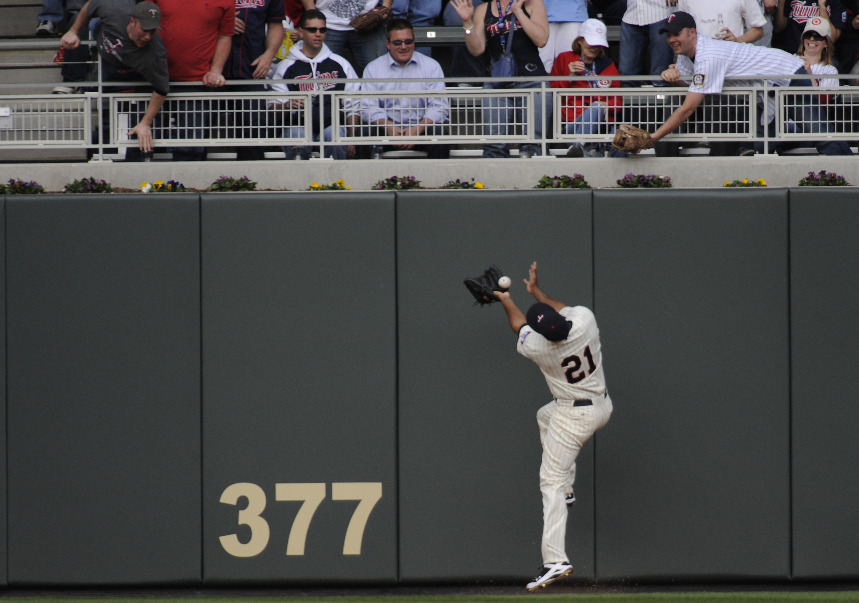 MINNESOTA, MN - APRIL 12: Delmon Young #21 of the Minnesota Twins bobbles the ball allowing Kevin Youkilis #20 of the Boston Red Sox to score in the fourth inning against the Boston Red Sox during the Twins home opener at Target Field on April 12, 2010 in