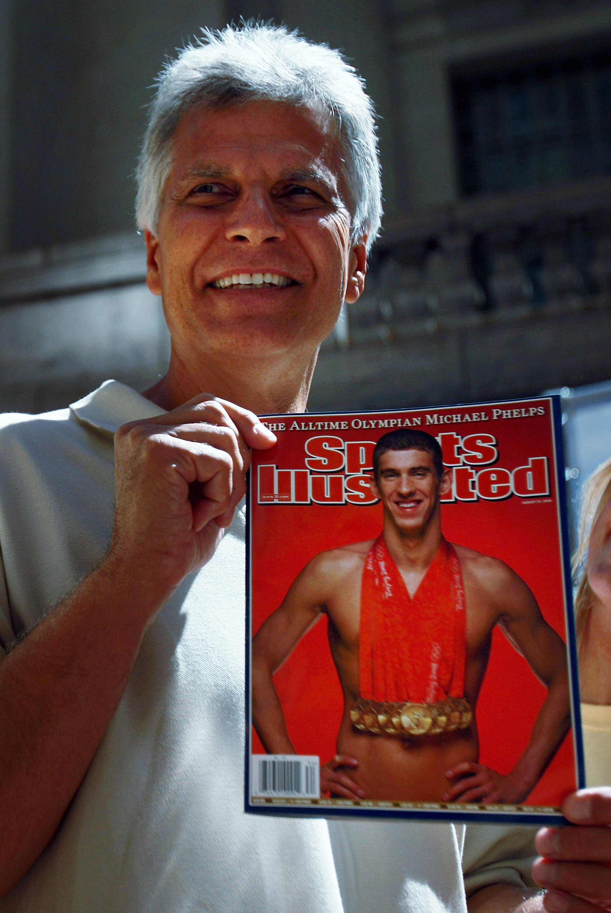 NEW YORK - AUGUST 20:  Swimmer Mark Spitz holds up a copy of the new issue of Sports Illustrated featuring a picture of Olympic swimmer Michael Phelps at Grand Central Station August 20, 2008 in New York City. Spitz's record of breaking seven world record