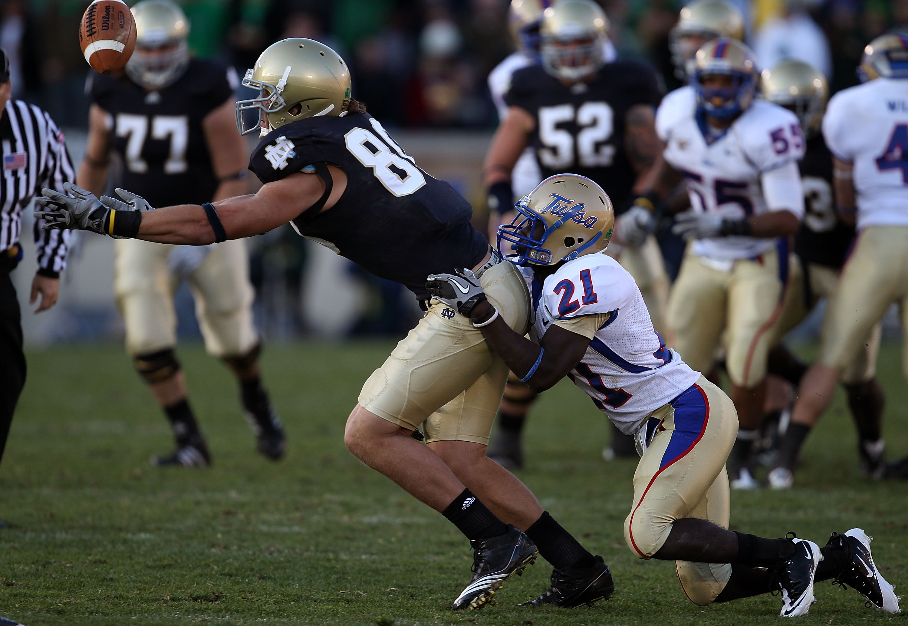 SOUTH BEND, IN - OCTOBER 30: Tyler Eifert #80 of the Notre Dame Fighting Irish drops a pass as he is hit by John Flanders #21 of the Tulsa Golden Hurricane at Notre Dame Stadium on October 30, 2010 in South Bend, Indiana. Tulsa defeated Notre Dame 28-27.