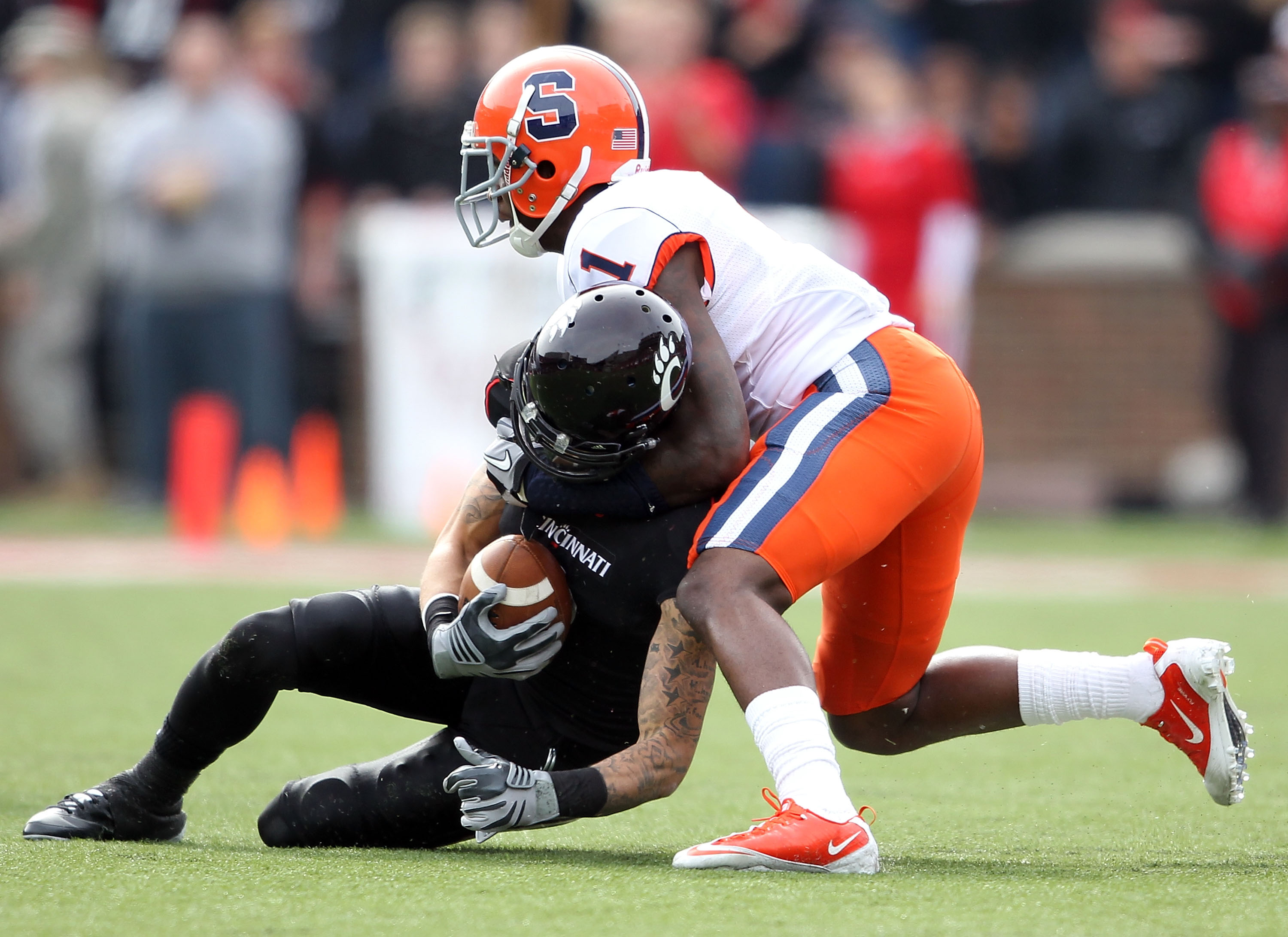 CINCINNATI - OCTOBER 30:  D J Woods #3 of the Cincinnati Bearcats is tackled by Phillip Thomas #1 of the Syracuse Orange during the Big East Conference game at Nippert Stadium on October 30, 2010 in Cincinnati, Ohio.  (Photo by Andy Lyons/Getty Images)
