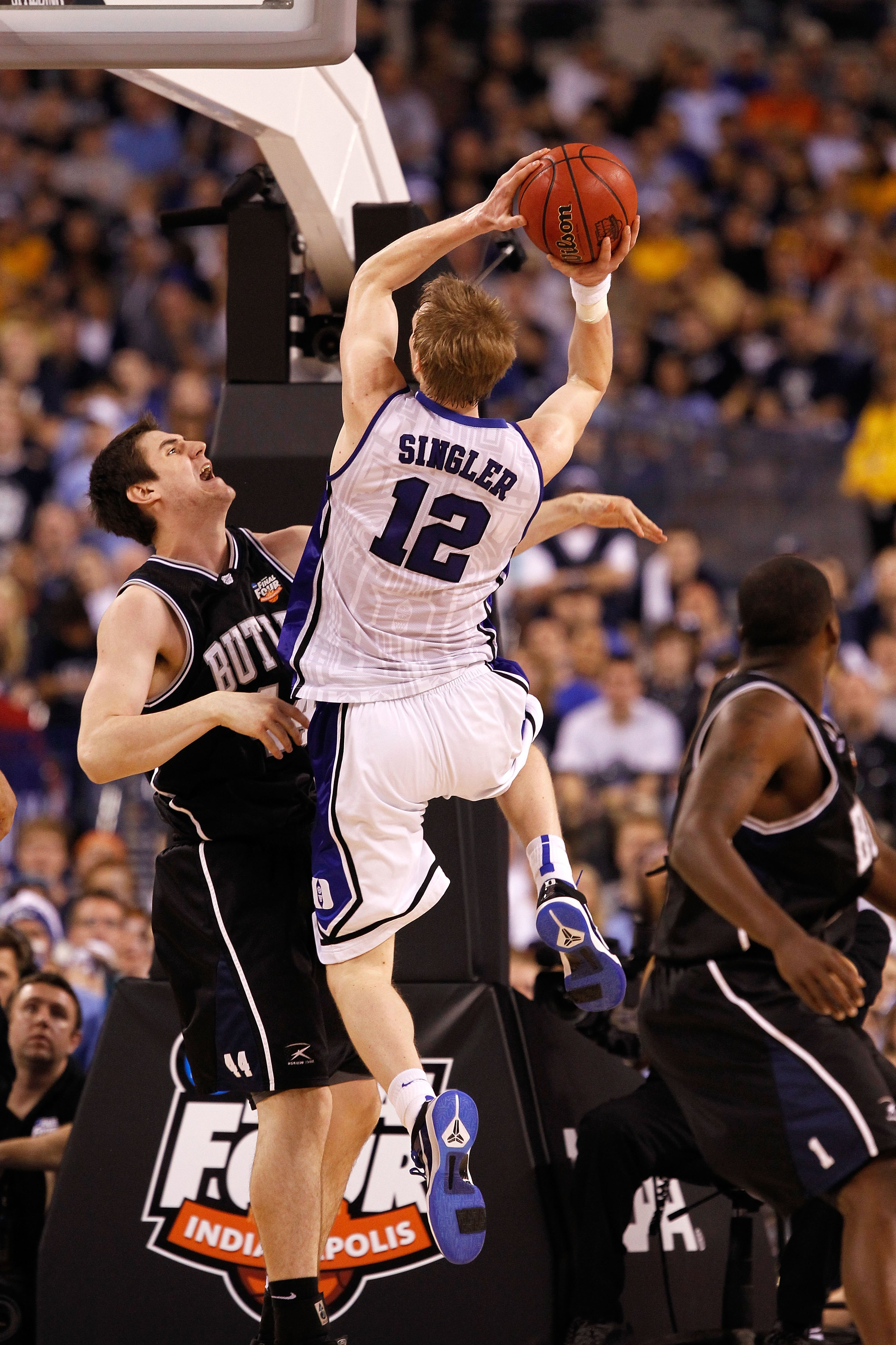 INDIANAPOLIS - APRIL 05:  Kyle Singler #12 of the Duke Blue Devils drives for a shot attempt against Andrew Smith #44 of the Butler Bulldogs during the 2010 NCAA Division I Men's Basketball National Championship game at Lucas Oil Stadium on April 5, 2010