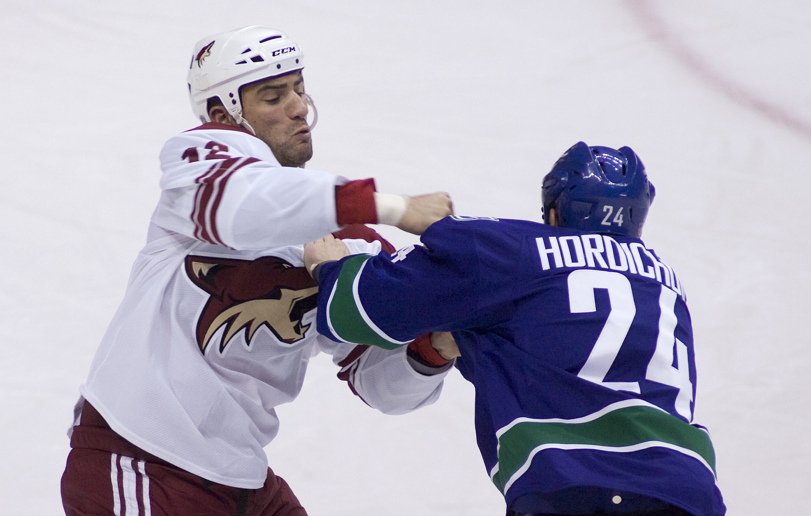 VANCOUVER, CANADA - JANUARY 7: Darcy Hordichuk #24 of the Vancouver Canucks and Paul Bissonnette #12 of the Phoenix Coyotes exchange punches during a fight in the third period of NHL action on January 07, 2010 at General Motors Place in Vancouver, British