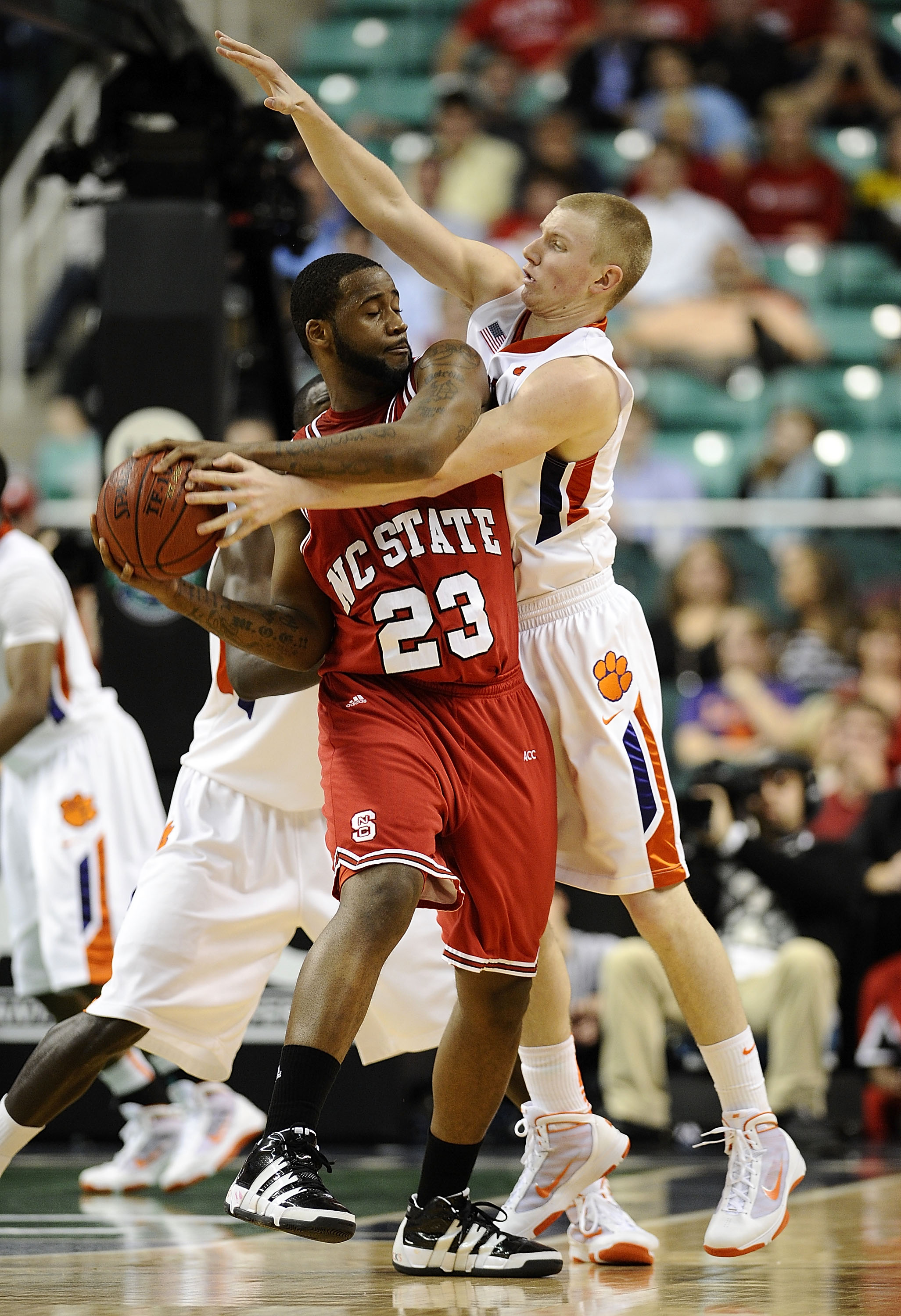 GREENSBORO, NC - MARCH 11:  Tanner Smith #5 of the Clemson Tigers guards Tracy Smith #23 of the North Carolina State Wolfpack in their first-round game in the 2010 ACC Men's Basketball Tournament at the Greensboro Coliseum on March 11, 2010 in Greensboro,