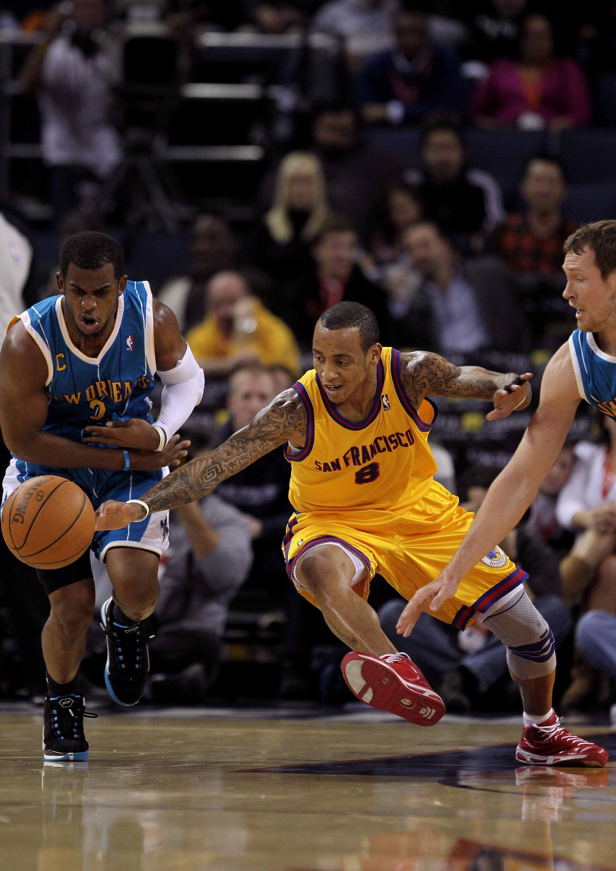 OAKLAND, CA - JANUARY 27:  Monta Ellis #8 of the Golden State Warriors and Chris Paul #3 of the New Orleans Hornets scramble for a loose ball at Oracle Arena on January 27, 2010 in Oakland, California.  NOTE TO USER: User expressly acknowledges and agrees