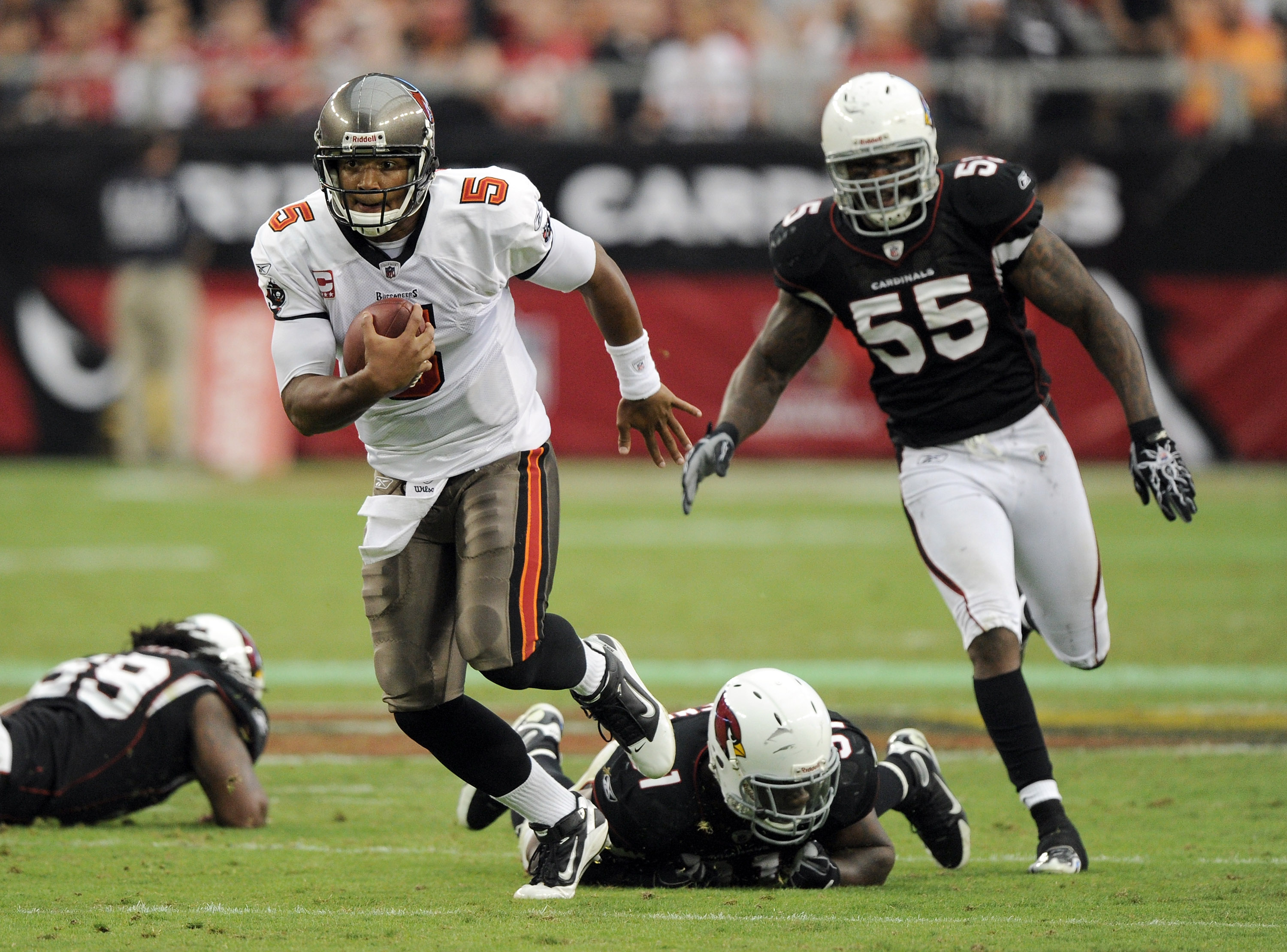GLENDALE, AZ - OCTOBER 31:  Josh Freeman #5 of the Tampa Bay Buccaneers scrambles away from Joey Porter #55, Kenny Iwebema #91 and Will Davis #59 of the Arizona Cardinals during the third quarter at University of Phoenix Stadium on October 31, 2010 in Gle