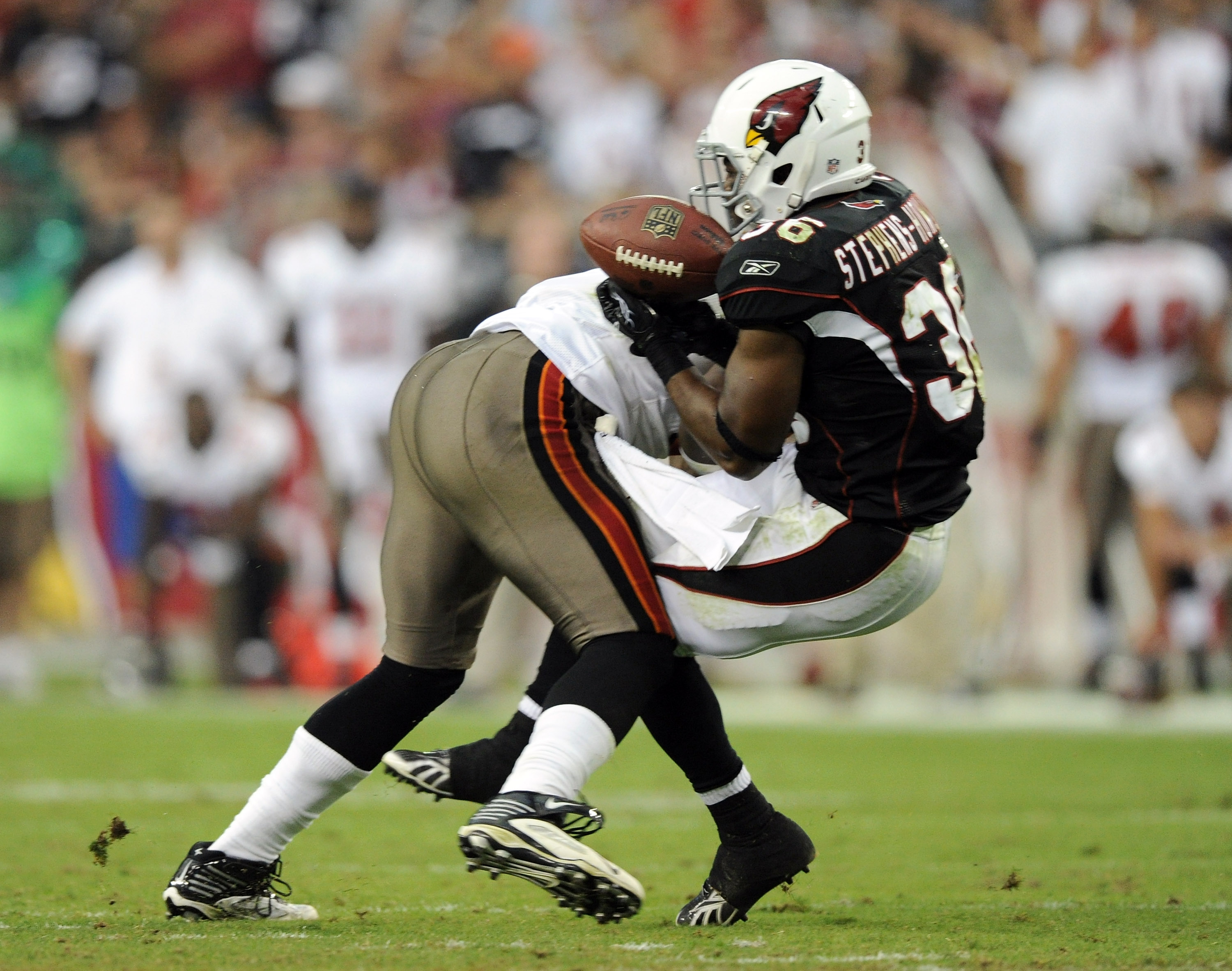 GLENDALE, AZ - OCTOBER 31:  LaRod Stephens-Howling #36 of the Arizona Cardinals takes a hit from Geno Hayes #54 of the Tampa Bay Buccaneers resulting in an interception and injury during the fourth quarter at University of Phoenix Stadium on October 31, 2
