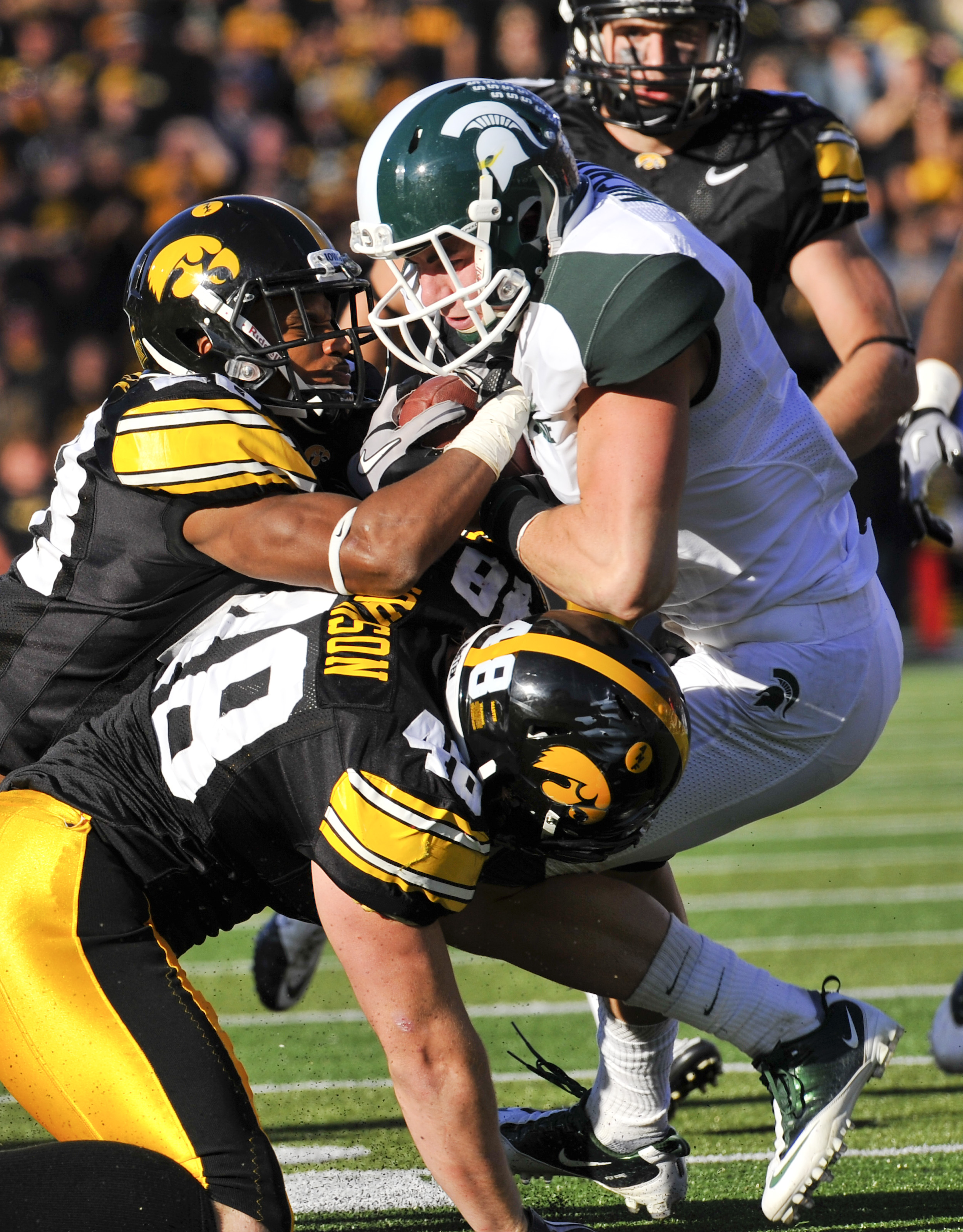 IOWA CITY, IA - OCTOBER 30: Line backer Troy Johnson #48 and defensive back Shaun Prater #28 of the University of Iowa Hawkeyes tackle wide receiver Keith Nichol #7 of the Michigan State Spartans during the first half of play at Kinnick Stadium on October