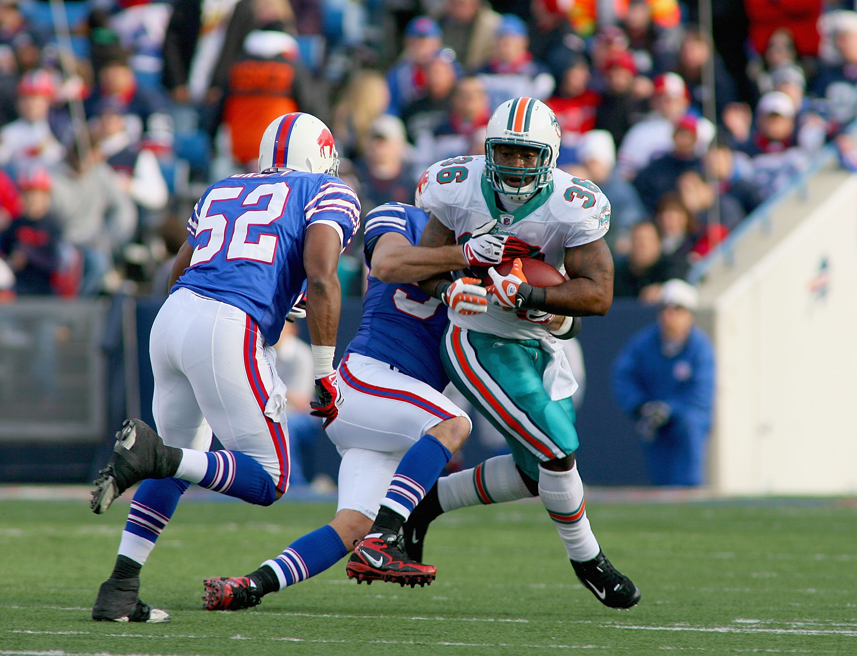 ORCHARD PARK, NY - NOVEMBER 29: Lousaka Polite #36 of the Miami Dolphins runs as Paul Posluszny #51 and Chris Draft #52 of the Buffalo Bills come in to make the tackle at Ralph Wilson Stadium on November 29, 2009 in Orchard Park, New York. Buffalo won 31-