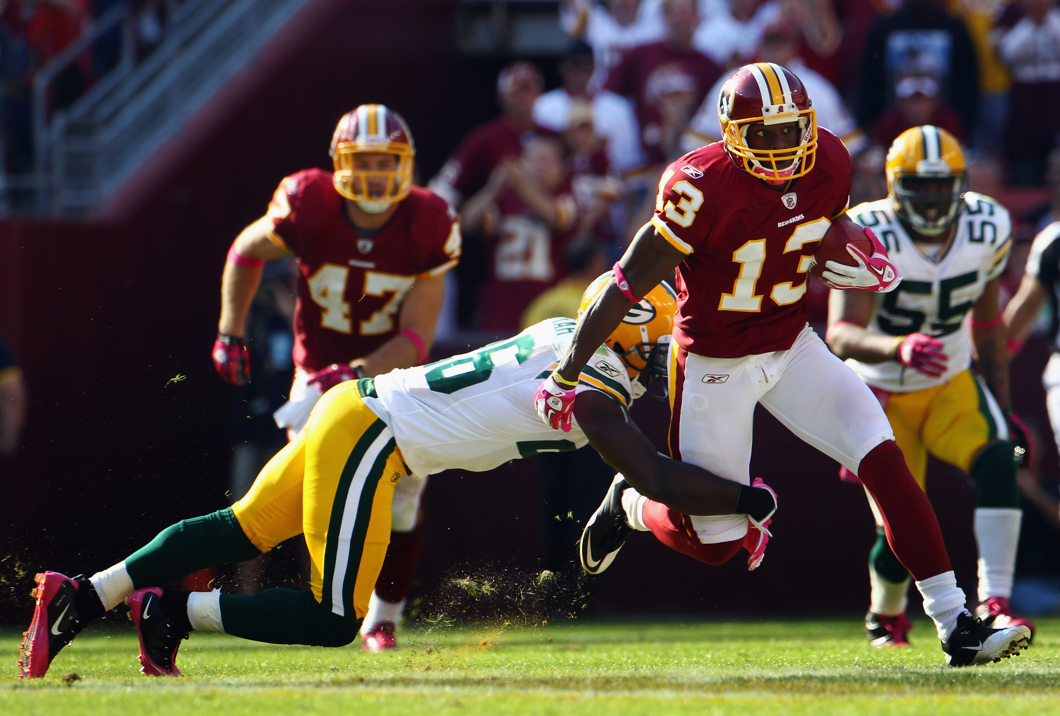 LANDOVER, MD - OCTOBER 10:  Wide receiver Anthony Armstrong #13 of the Washington Redskins runs after a catch while being tackled by defensive back Josh Bell #26 of the Green Bay Packers in the fourth quarter at FedExField on October 10, 2010 in Landover,
