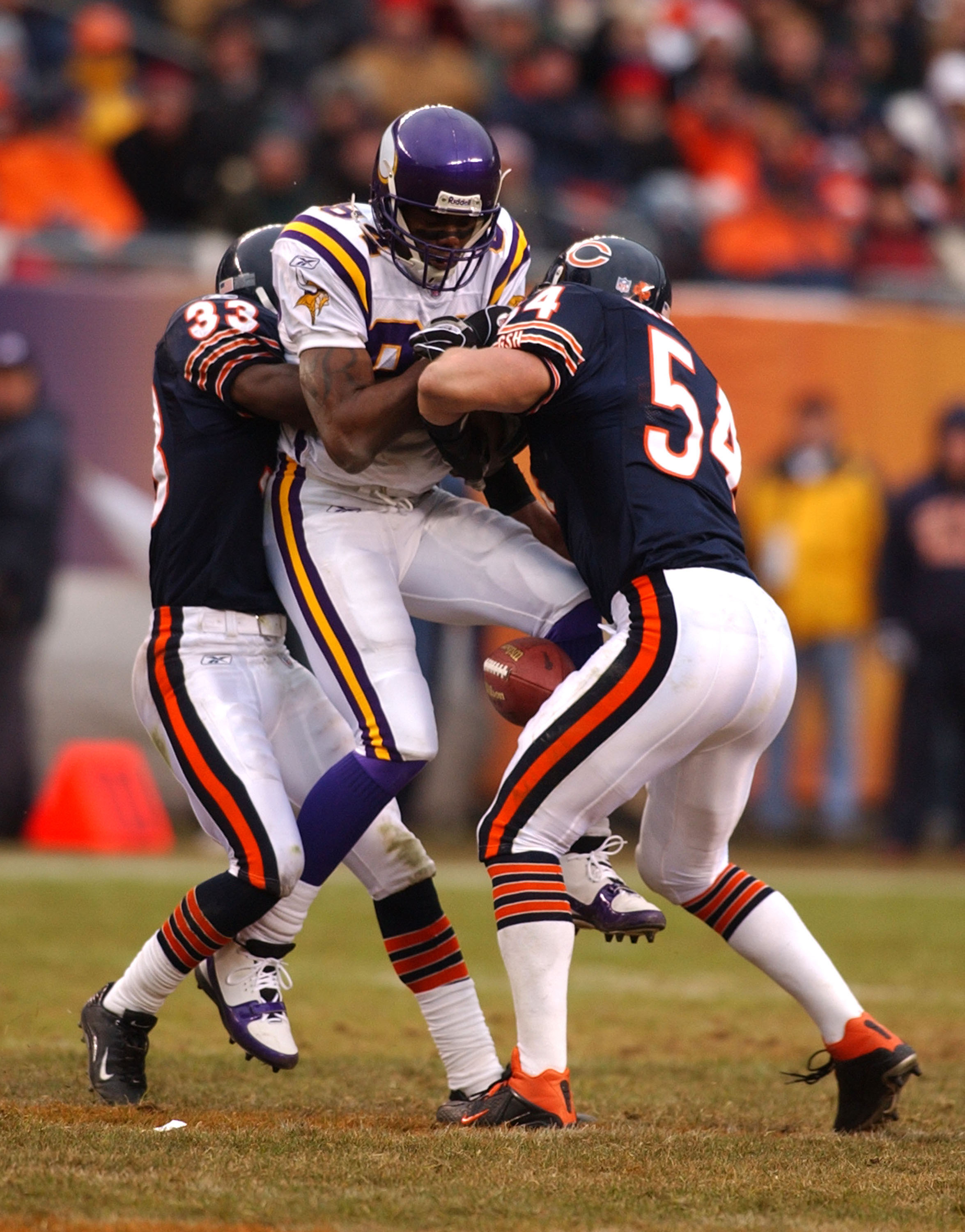 CHICAGO - DECEMBER 14: Receiver Randy Moss #84 of the Minnesota Vikings is hit and drops the ball by linebacker Brian Urlacher #54 and cornerback Charles Tillman #33 of the Chicago Bears during a game on December 14, 2003 at Soldier Field in Chicago, Illi