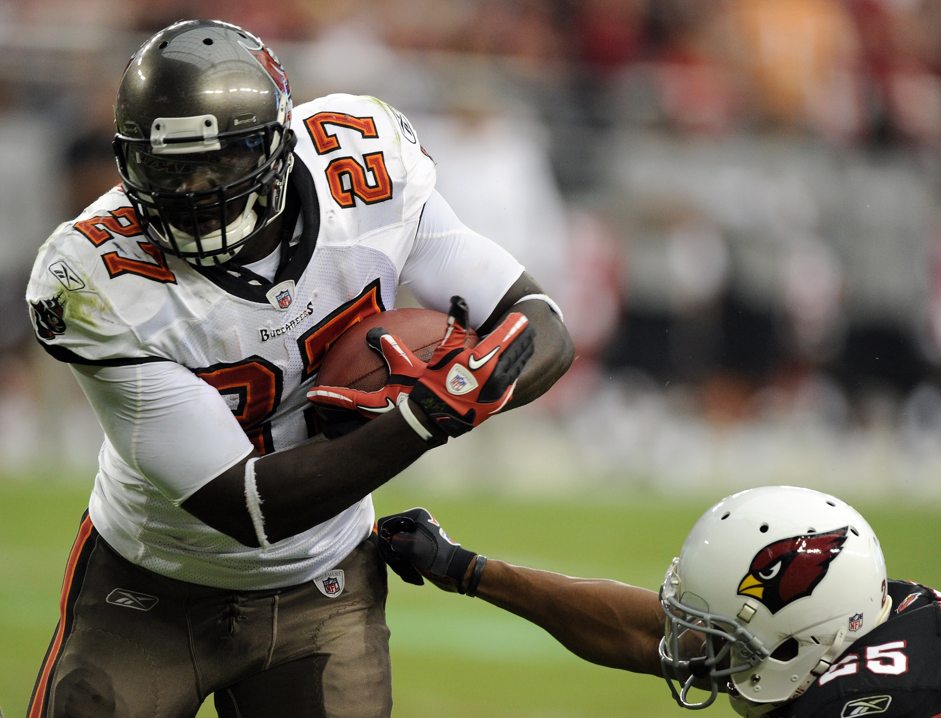 GLENDALE, AZ - OCTOBER 31:  LaGarrette Blount #27 of the Tampa Bay Buccaneers gets away from Kerry Rhodes #25 of the Arizona Cardinals at University of Phoenix Stadium on October 31, 2010 in Glendale, Arizona.  (Photo by Harry How/Getty Images)