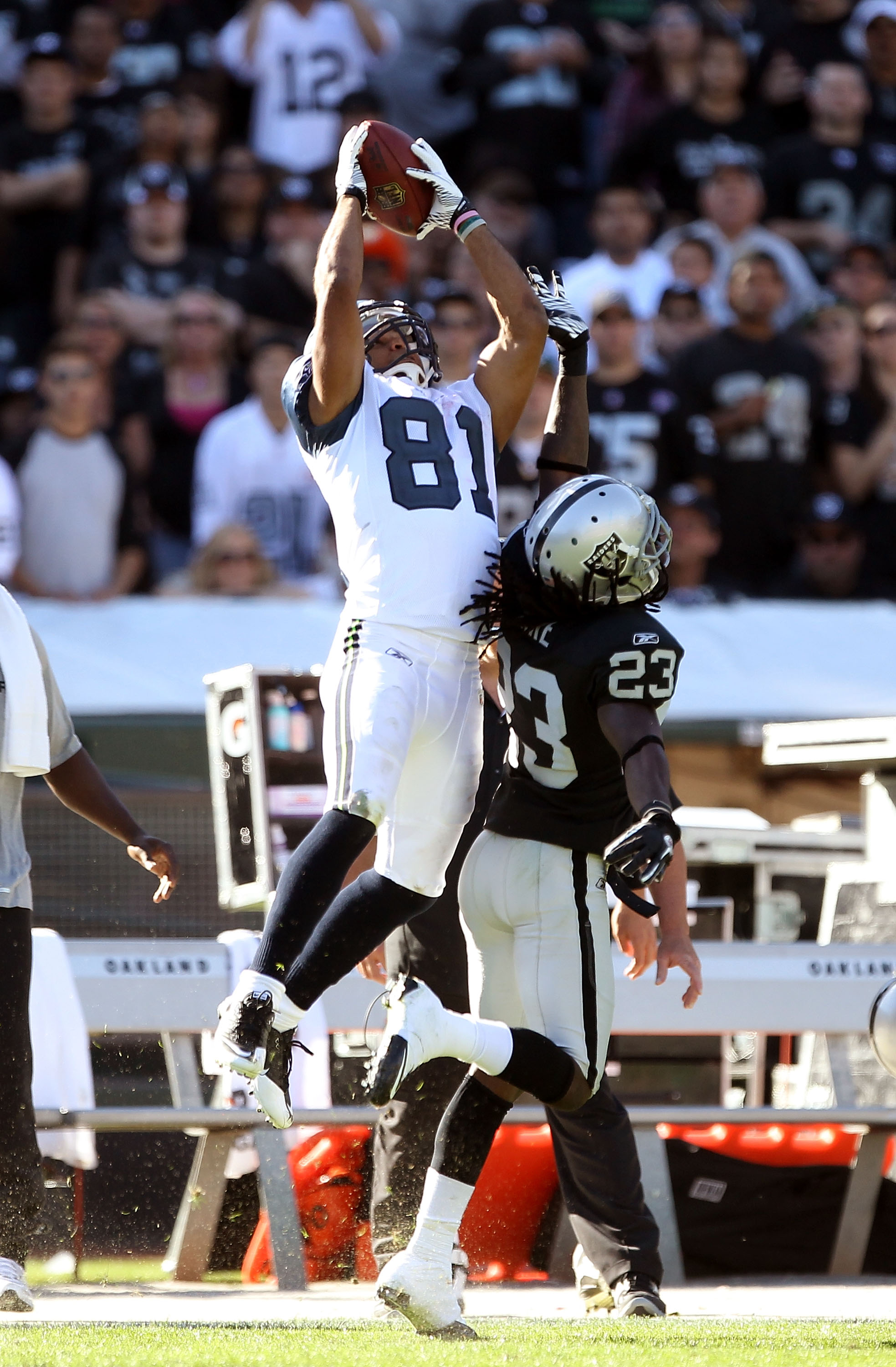 OAKLAND, CA - OCTOBER 31:  Golden Tate #81 of the Seattle Seahawks makes a leaping catch over Jeremy Ware #23 of the Oakland Raiders at Oakland-Alameda County Coliseum on October 31, 2010 in Oakland, California.  (Photo by Ezra Shaw/Getty Images)