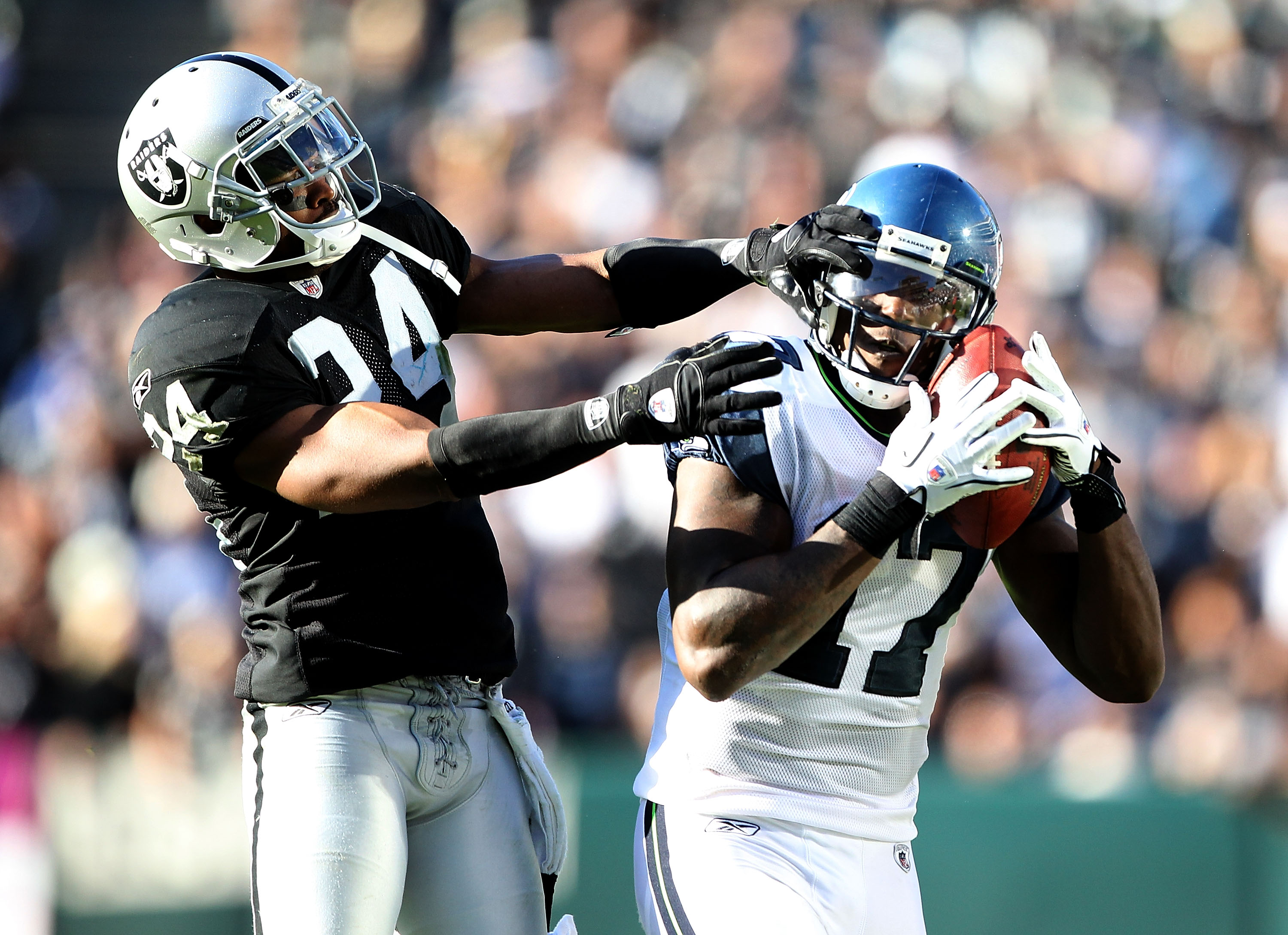 OAKLAND, CA - OCTOBER 31:  Mike Williams #17 of the Seattle Seahawks catches the ball while defended by Michael Huff #24 of the Oakland Raiders at Oakland-Alameda County Coliseum on October 31, 2010 in Oakland, California.  (Photo by Ezra Shaw/Getty Image