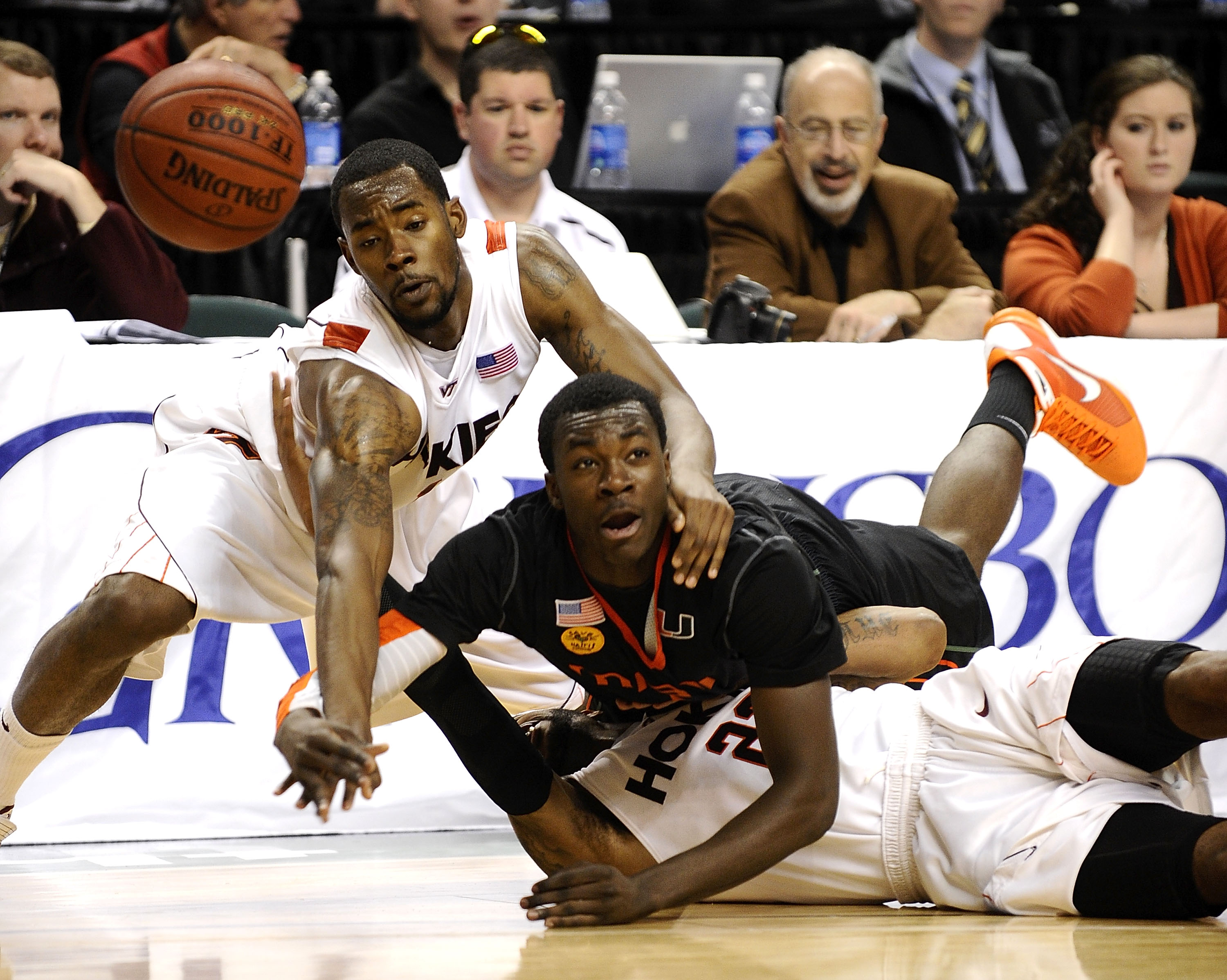 GREENSBORO, NC - MARCH 12:  Malcolm Delaney #23 and Terrell Bell #1 of the Virginia Tech Hokies fights for a loose ball with Durand Scott #1  of the University of Miami Hurricanes in their quarterfinal game in the 2010 ACC Men's Basketball Tournament at t