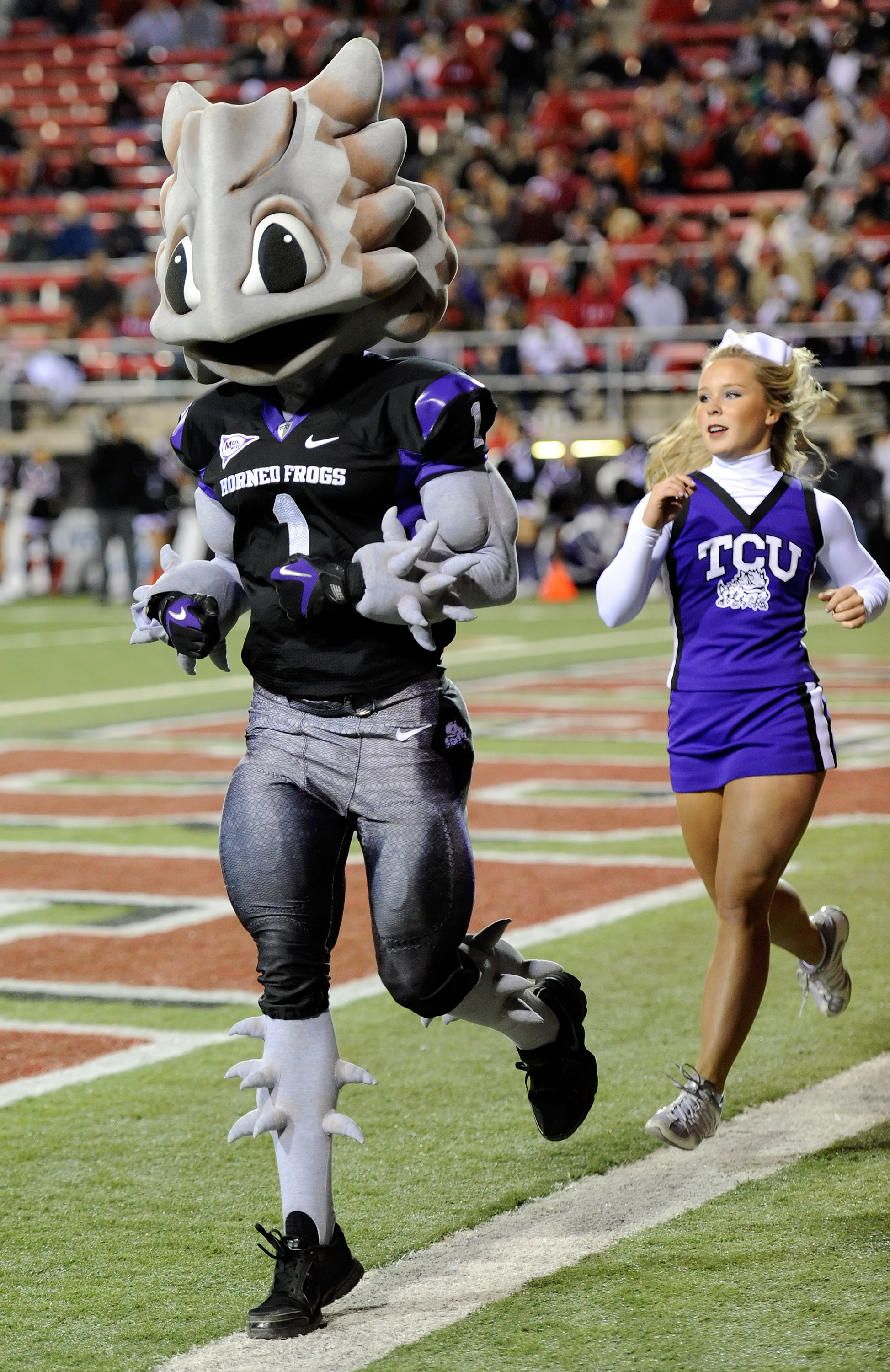 LAS VEGAS - OCTOBER 30:  Texas Christian University Horned Frogs mascot 'Superfrog' and a cheerleader run along the end zone after the team scored against the UNLV Rebels at Sam Boyd Stadium October 30, 2010 in Las Vegas, Nevada. TCU won 48-6.  (Photo by