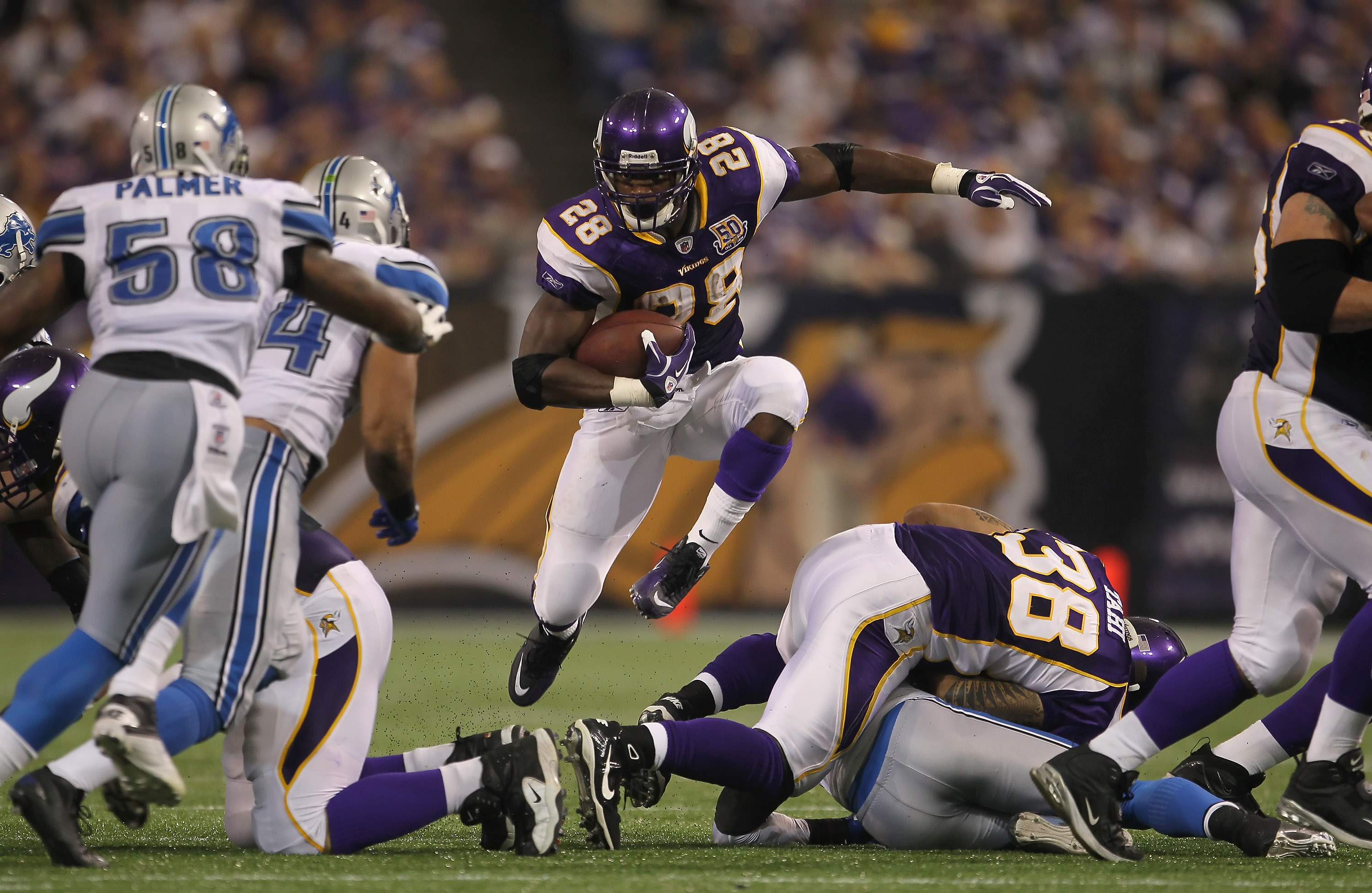 MINNEAPOLIS - SEPTEMBER 26:  Running back Adrian Peterson #28 of the Minnesota Vikings jumps through a hole while carrying the ball against the Detroit Lions during the second half at Hubert H. Humphrey Metrodome on September 26, 2010 in Minneapolis, Minn