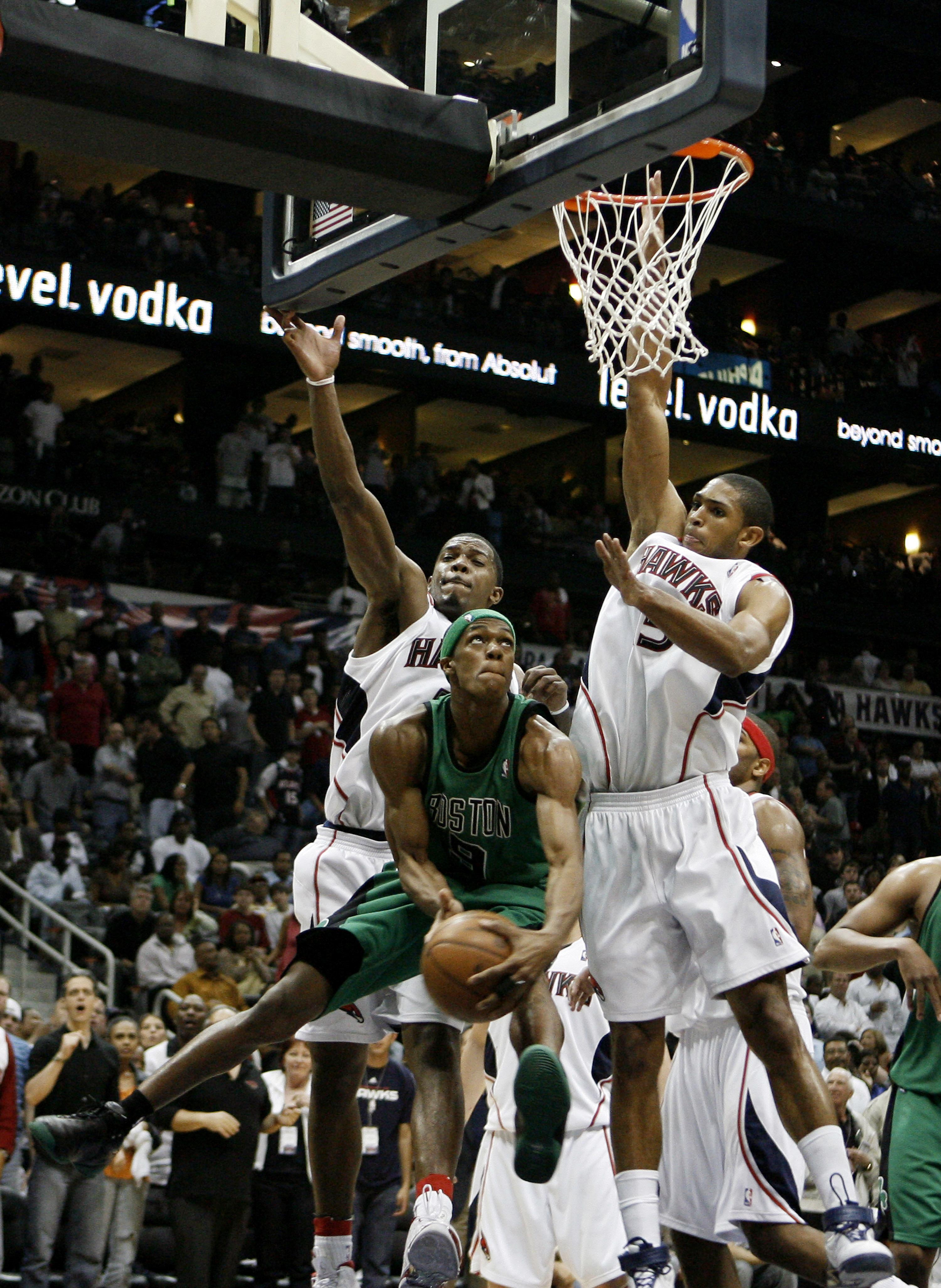 ATLANTA - APRIL 26:  Guard Rajon Rondo #9 of the Boston Celtics tries to score around defenders Al Horford #15 and Joe Johnson #2 of the Atlanta Hawks during Game Three of the Eastern Conference Quarterfinals against the Atlanta Hawks during the 2008 NBA