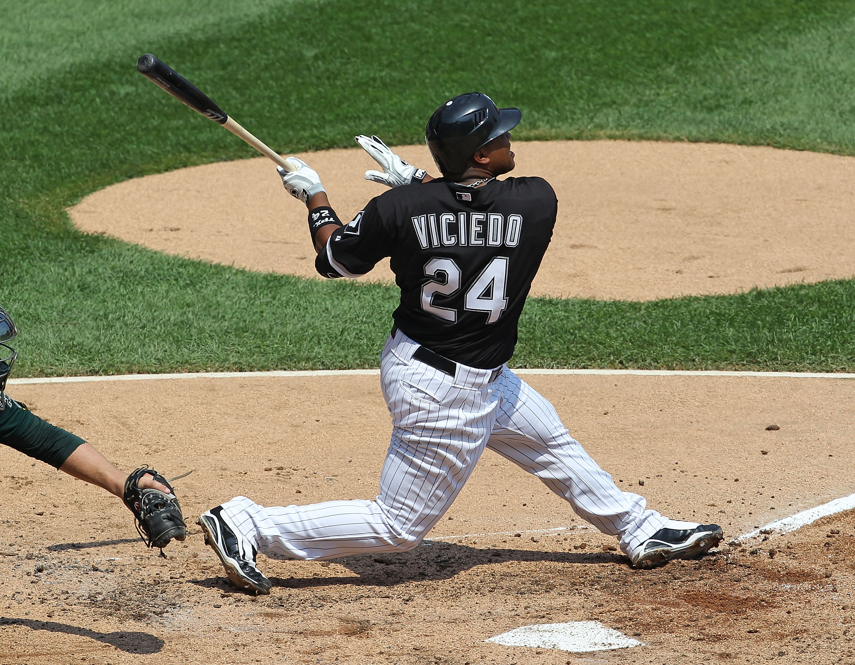 CHICAGO - AUGUST 01: Dayan Viciedo #24 of the Chicago White Sox hits the ball against the Oakland Athletics at U.S. Cellular Field on August 1, 2010 in Chicago, Illinois. The White Sox defeated the Athletics 4-1. (Photo by Jonathan Daniel/Getty Images)