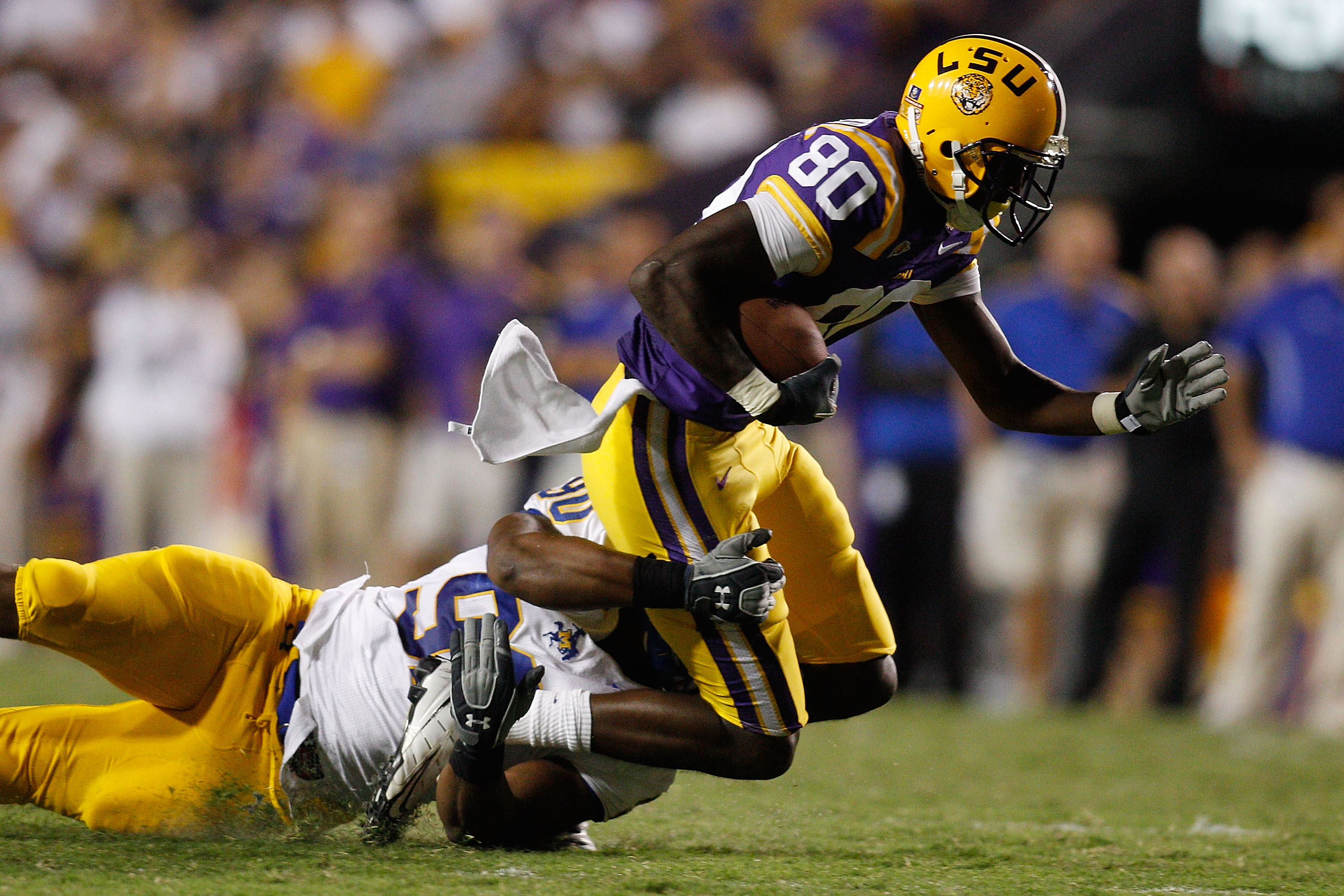 BATON ROUGE, LA - OCTOBER 16:   Terrence Toliver #80 of the Louisiana State University Tigers is tackled by Pat Williams #90 of the McNeese State Cowboys at Tiger Stadium on October 16, 2010 in Baton Rouge, Louisiana.  The Tigers defeated the Cowboys 32-1