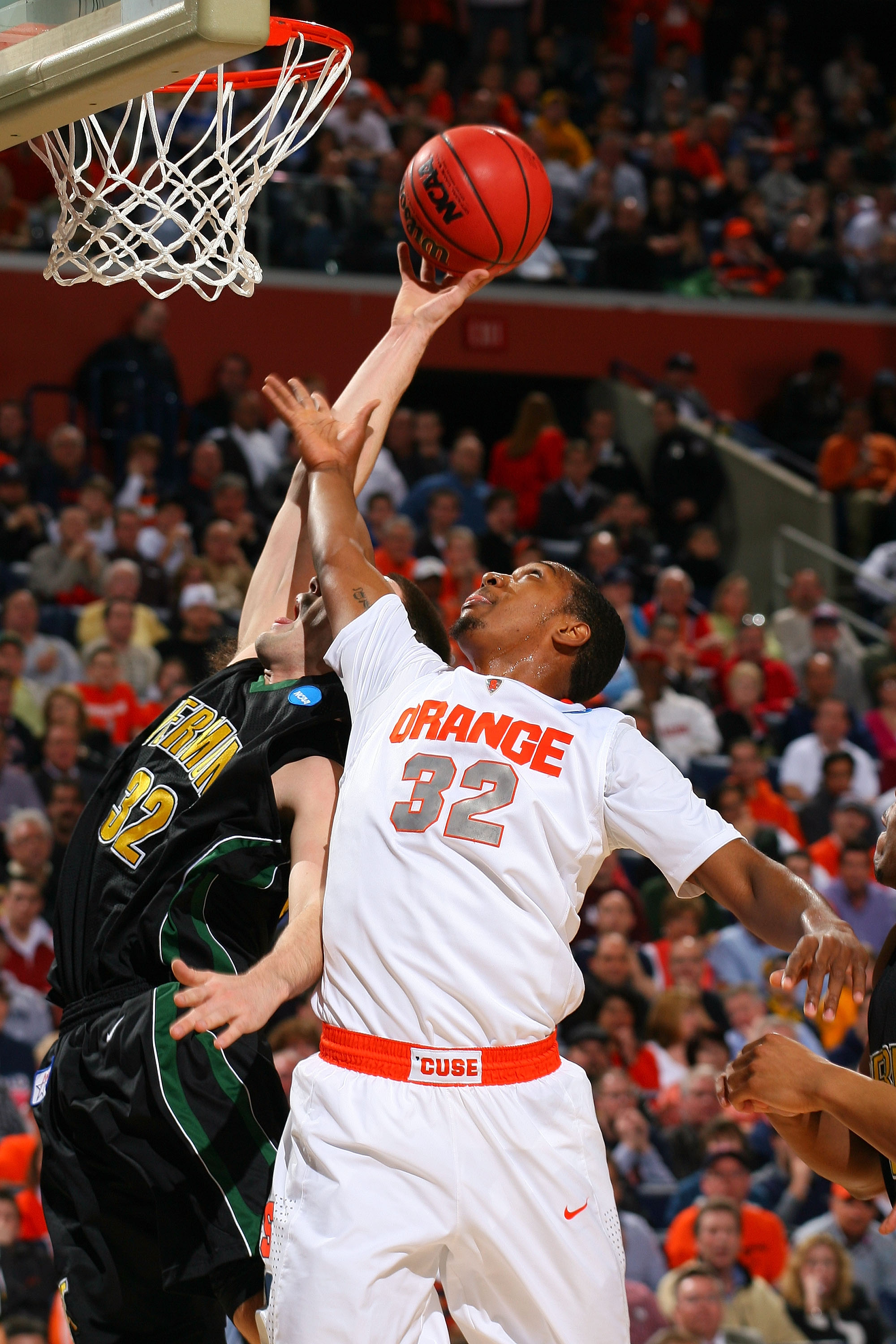BUFFALO, NY - MARCH 19:  Evan Fjeld #32 of the Vermont Catamounts goes to the hoop against Kris Joseph #32 of the Syracuse Orange during the first round of the 2010 NCAA men's basketball tournament at HSBC Arena on March 19, 2010 in Buffalo, New York.  (P