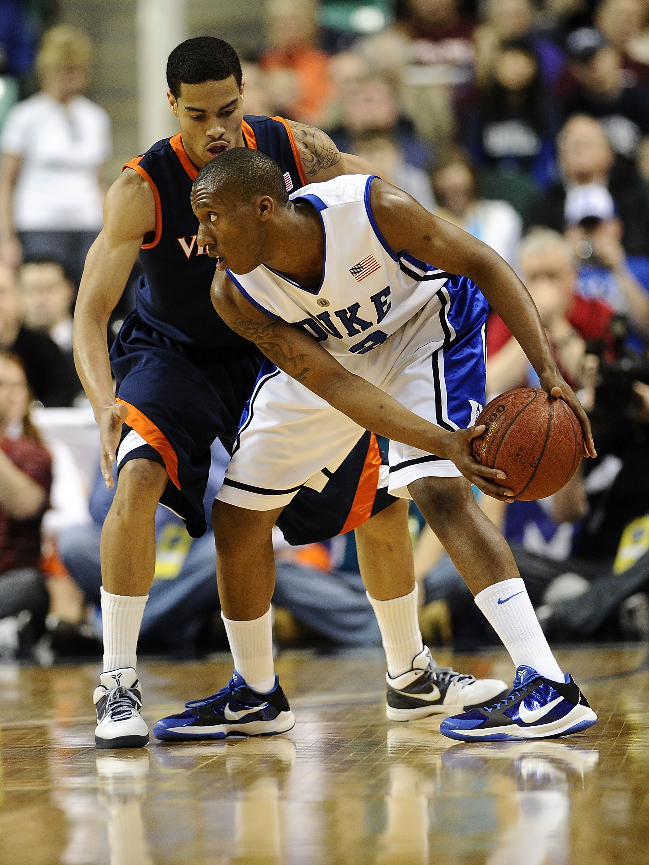 GREENSBORO, NC - MARCH 12:  Nolan Smith #2 of the Duke Blue Devils looks to get by Mike Scott #32 of the University of Virginia Cavaliers in their quarterfinal game in the 2010 ACC Men's Basketball Tournament at the Greensboro Coliseum on March 12, 2010 i
