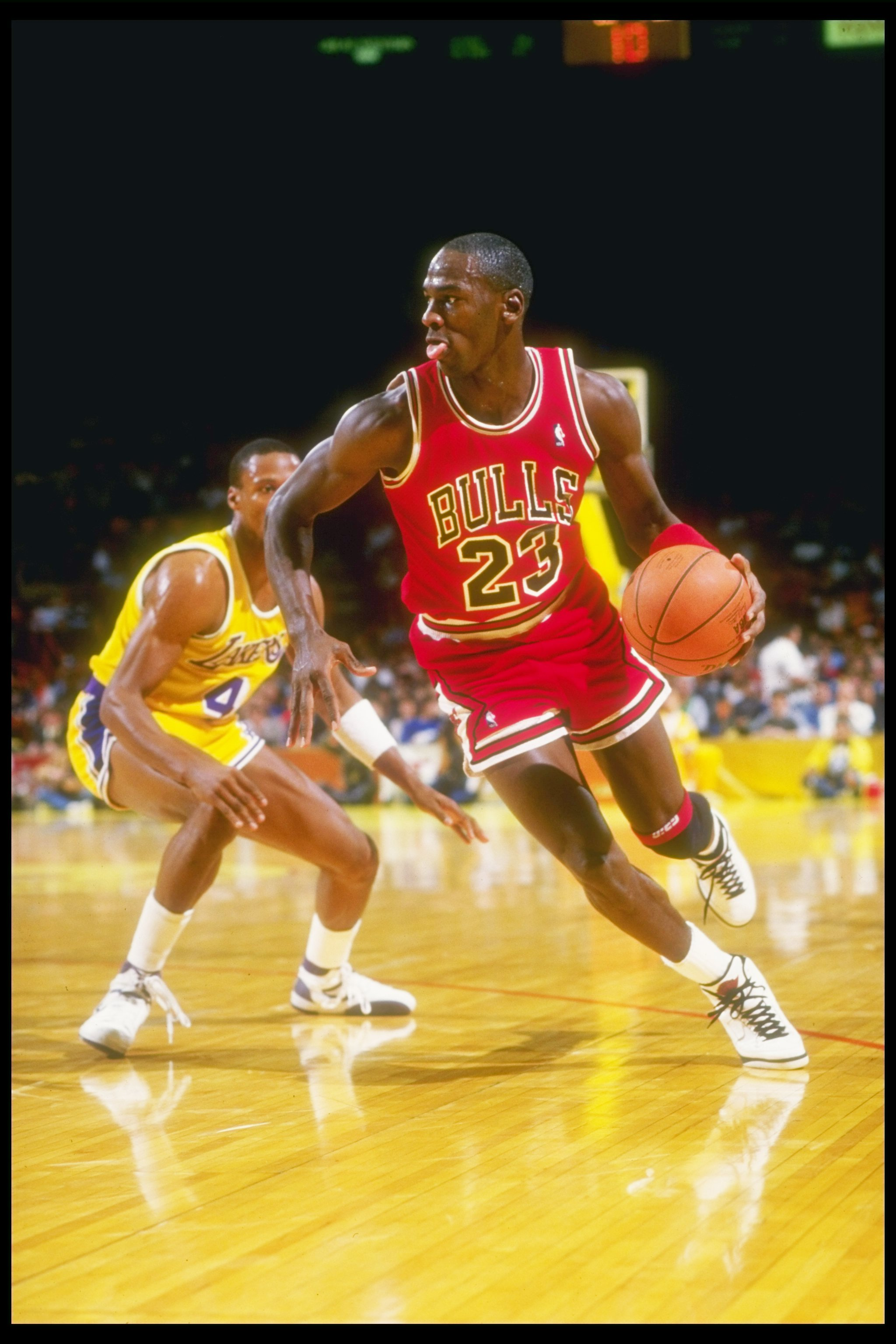 1986-1987:  Guard Michael Jordan (right) of the Chicago Bulls swiftly moves away from guard Byron Scott of the Los Angeles Lakers during a game held at The Forum in Inglewood, California. Mandatory Credit: Stephen Dunn  /Allsport
