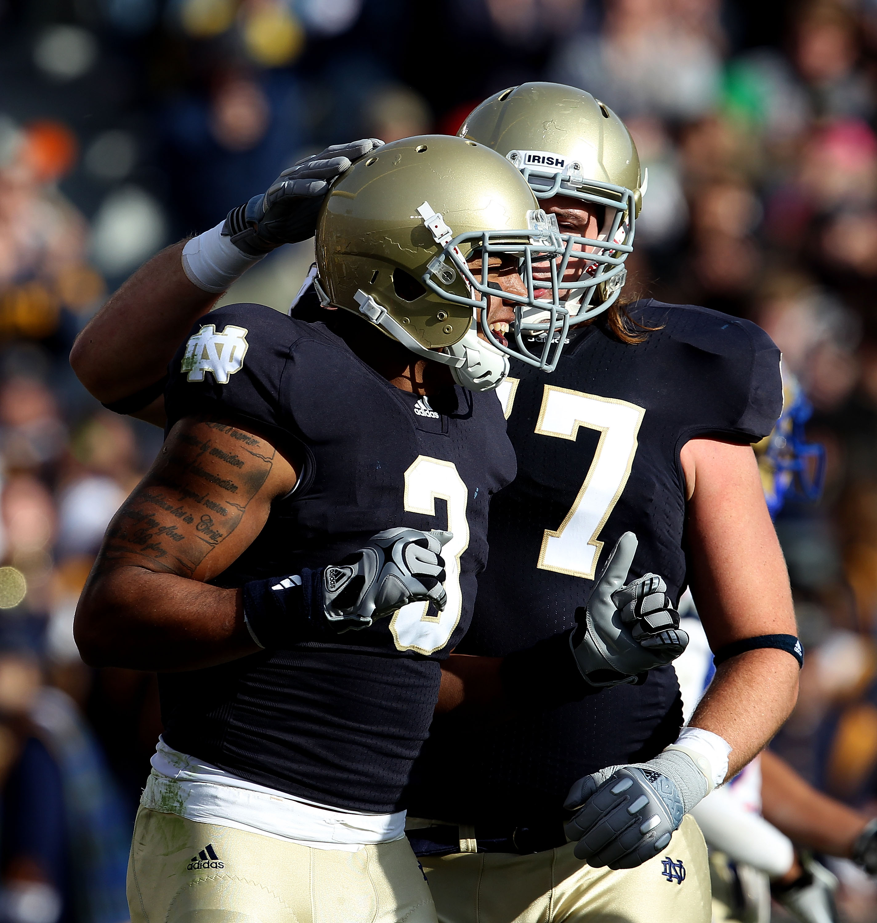 SOUTH BEND, IN - OCTOBER 30: Matt Romine #77 of the Notre Dame Fighting Irish congratulates teammate Michael Floyd #3 after a touchdown against the Tulsa Golden Hurricane at Notre Dame Stadium on October 30, 2010 in South Bend, Indiana. Tulsa defeated Not
