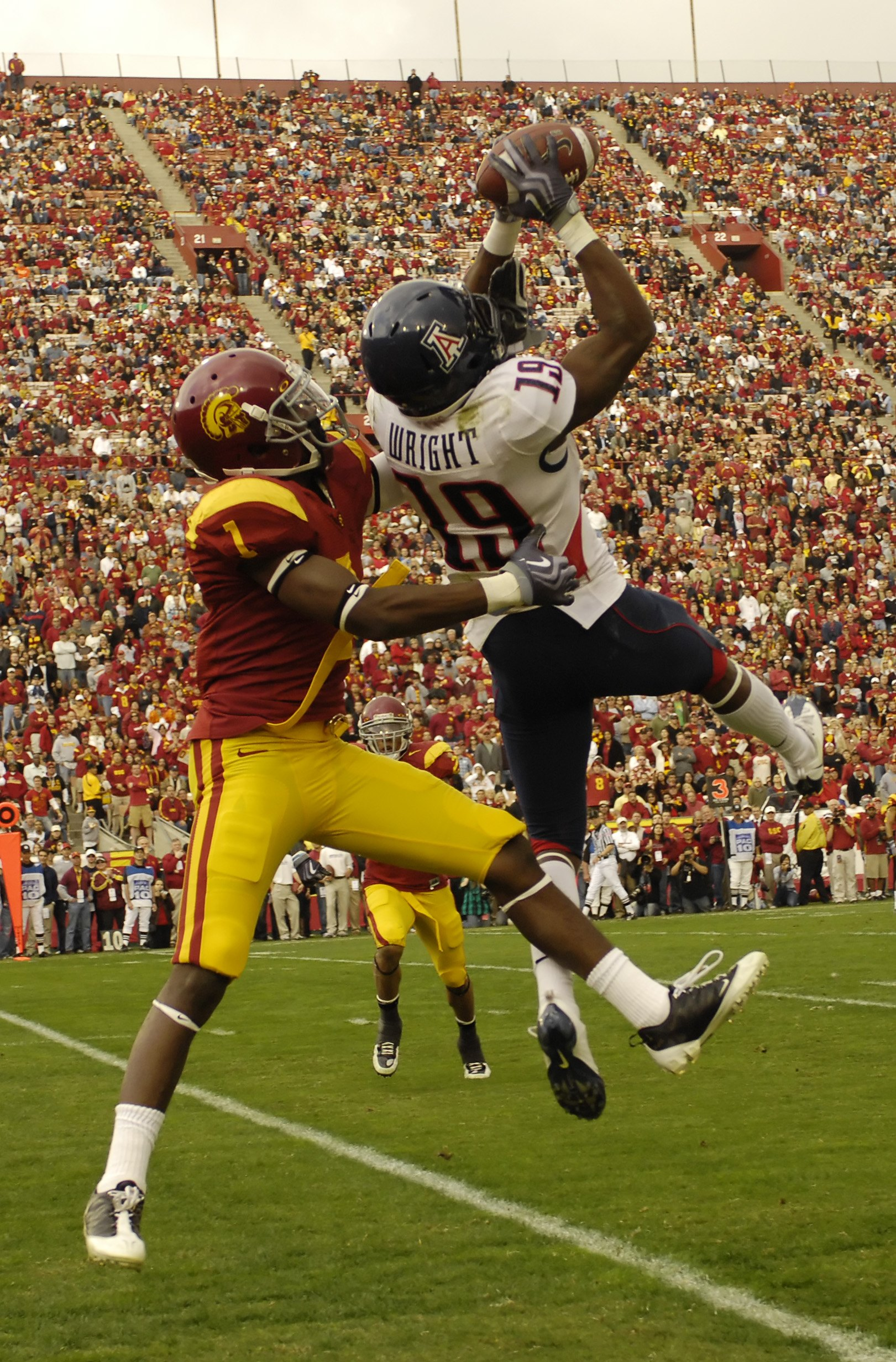 LOS ANGELES, CA - DECEMBER 05: Wide receiver William Wright #19 of the Arizona Wildcats catches a pass for a 19-yard gain against corner back T.J. Bryant #1 of the USC Trojans on the two yard line during the second quarter of the NCAA college football gam