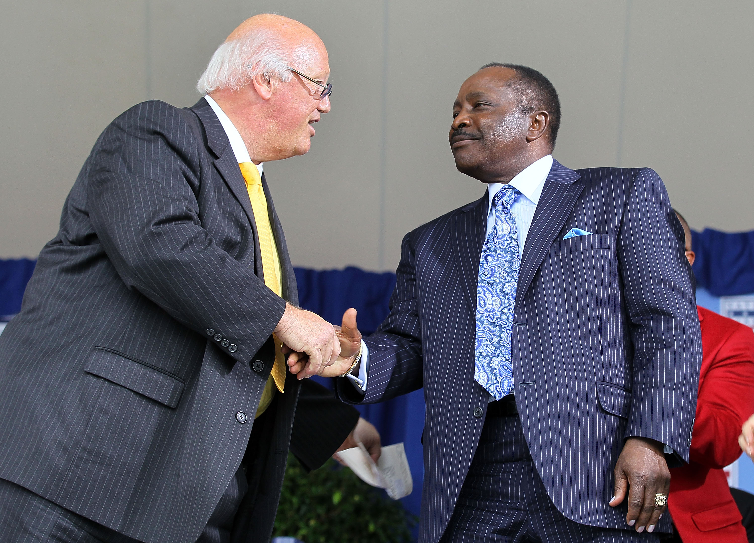 COOPERSTOWN, NY - JULY 25:  Jon Miller (L) shakes hands with Hall of Famer Joe Morgan after Miller received the Ford C. Frick award for contributions in baseball broadcasting at Clark Sports Center during the Baseball Hall of Fame induction ceremony on Ju