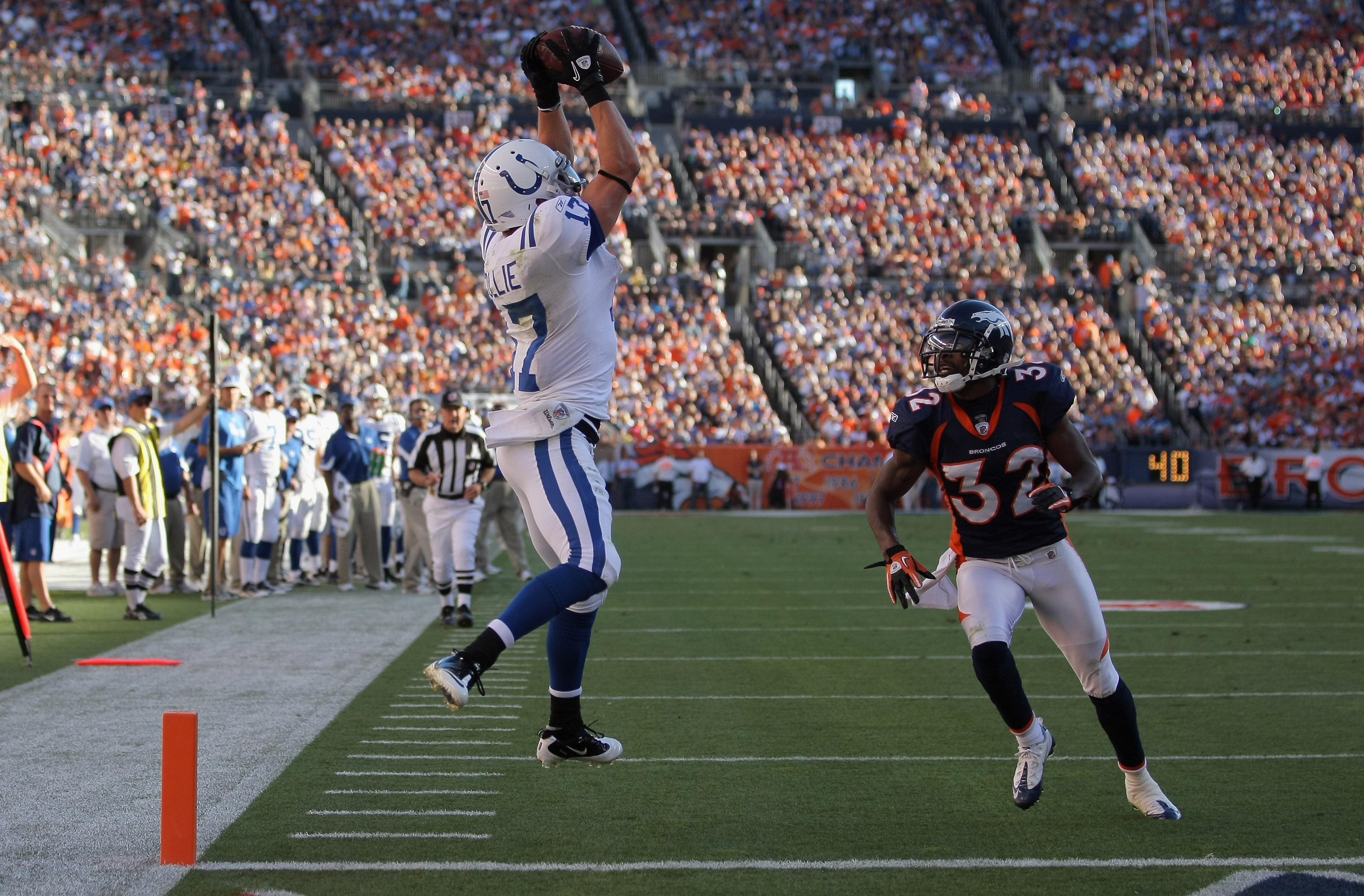 DENVER - SEPTEMBER 26:  Wide receiver Austin Collie #17 of the Indianapolis Colts makes a 23 yard touchdown reception in the fourth quarter as Perrish Cox #32 of the Denver Broncos defends at INVESCO Field at Mile High on September 26, 2010 in Denver, Col