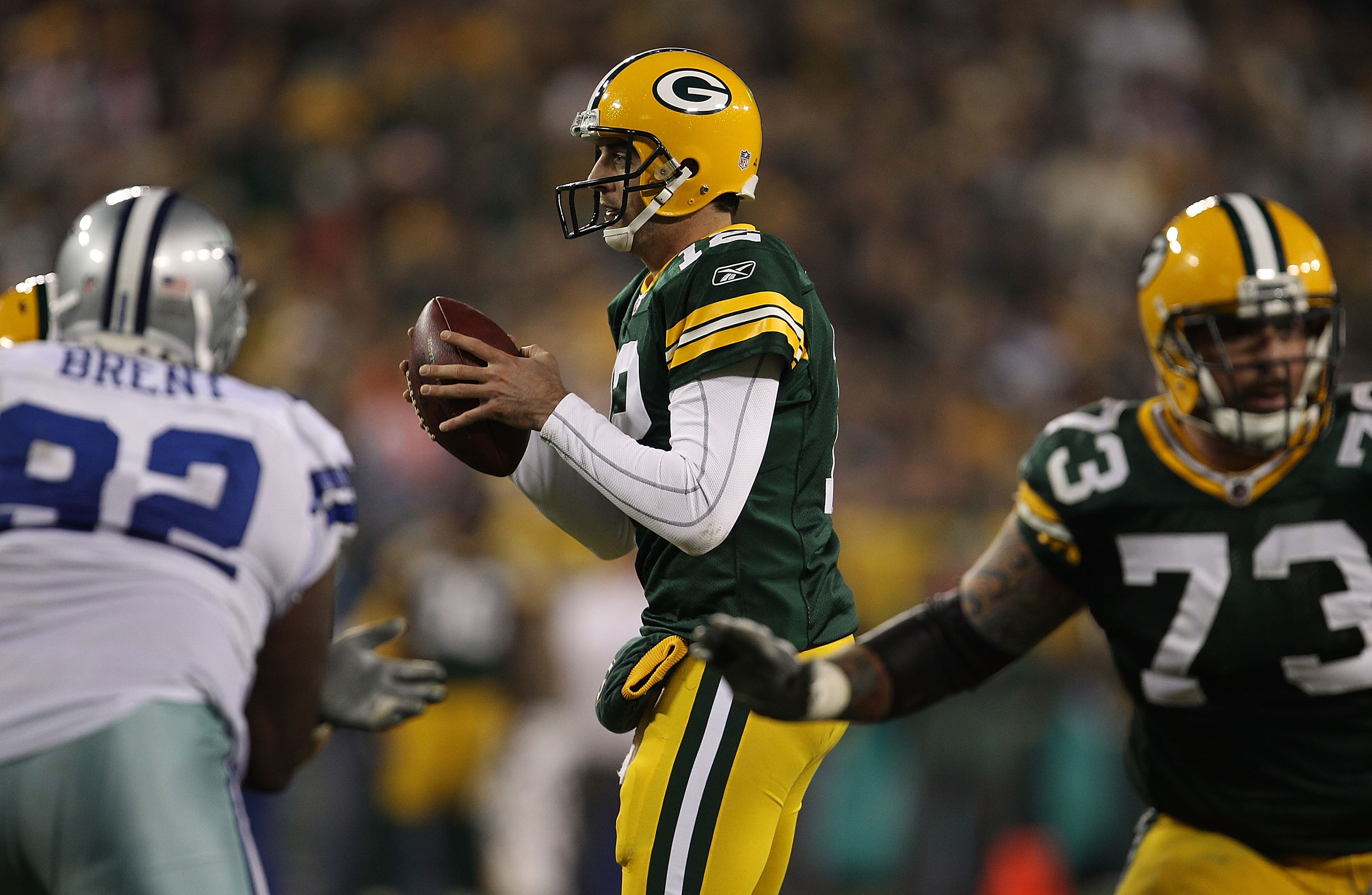 GREEN BAY, WI - NOVEMBER 07: Aaron Rodgers #12 of the Green Bay Packers takes the snap as teammate Daryn Colledge #73 looks to block and Josh Brent #92 of the Dallas Cowboys rushes at Lambeau Field on November 7, 2010 in Green Bay, Wisconsin. The Packers