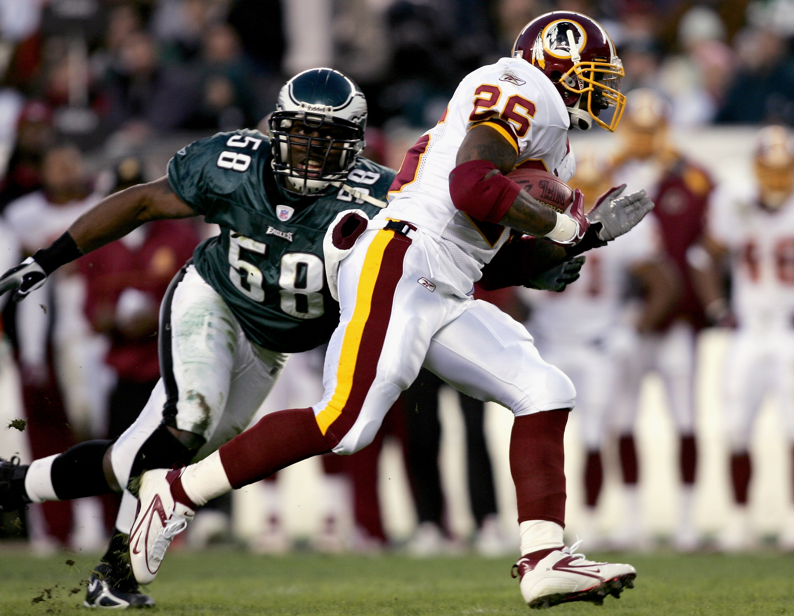 PHILADELPHIA - JANUARY 01:  Runningback Clinton Portis #26 of the Washington Redskins carries the ball away from Trent Cole #58 of the Philadelphia Eagles during the first quarter of the game on January 1, 2006 at Lincoln Financial Field in Philadelphia,