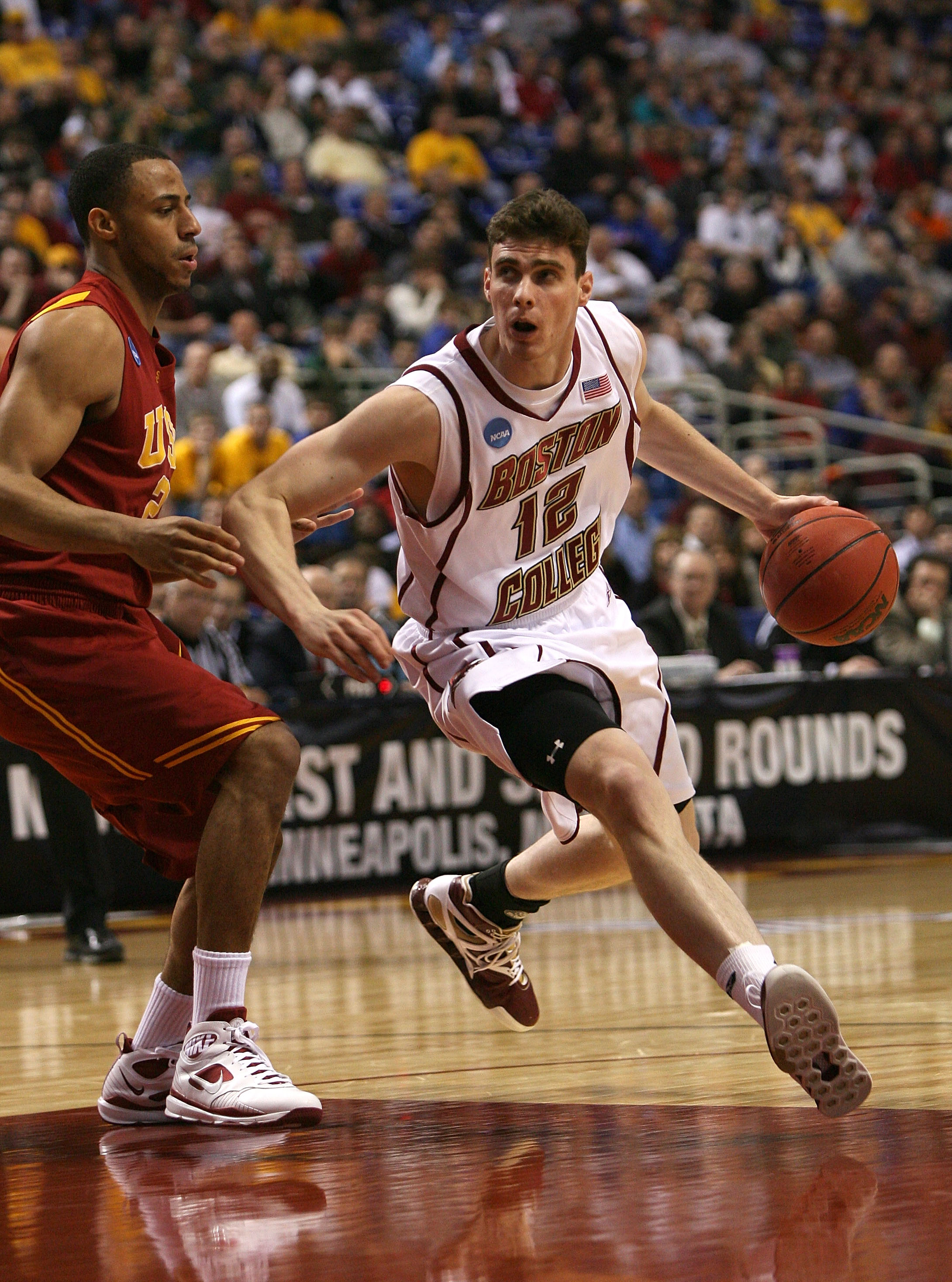 MINNEAPOLIS - MARCH 20:  Joe Trapani #12 of the Boston College Eagles drives against Dwight Lewis #21 of the USC Trojans during the first round of the NCAA Division I Men's Basketball Tournament at the Hubert H. Humphrey Metrodome on March 20, 2009 in Min