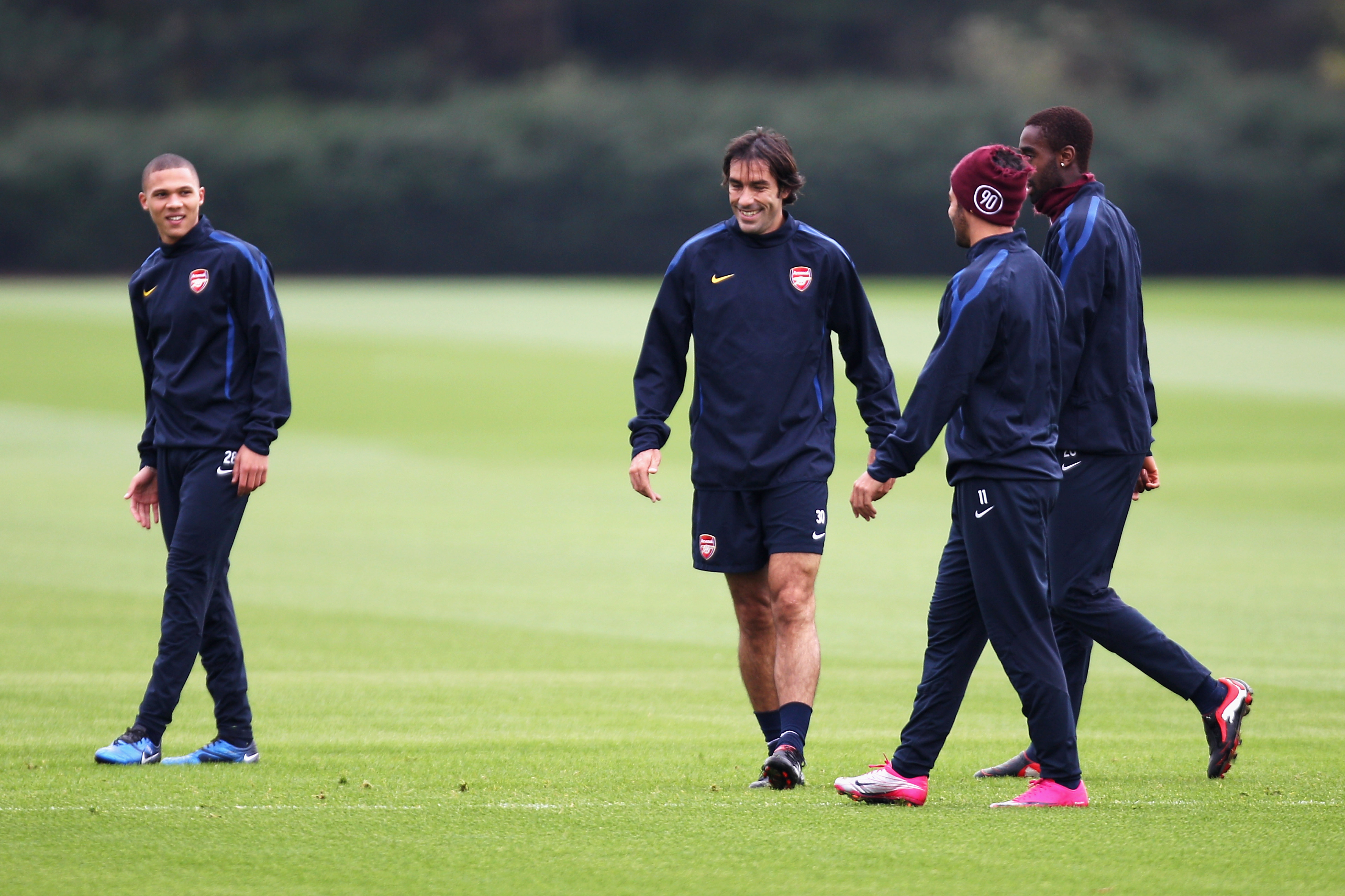 ST ALBANS, ENGLAND - OCTOBER 18:  Former Arsenal player Robert Pires (C) shares a joke with players during a training session ahead of the UEFA Champions League game against Shakhtar Donetsk at the club's complex at London Colney on October 18, 2010 in St