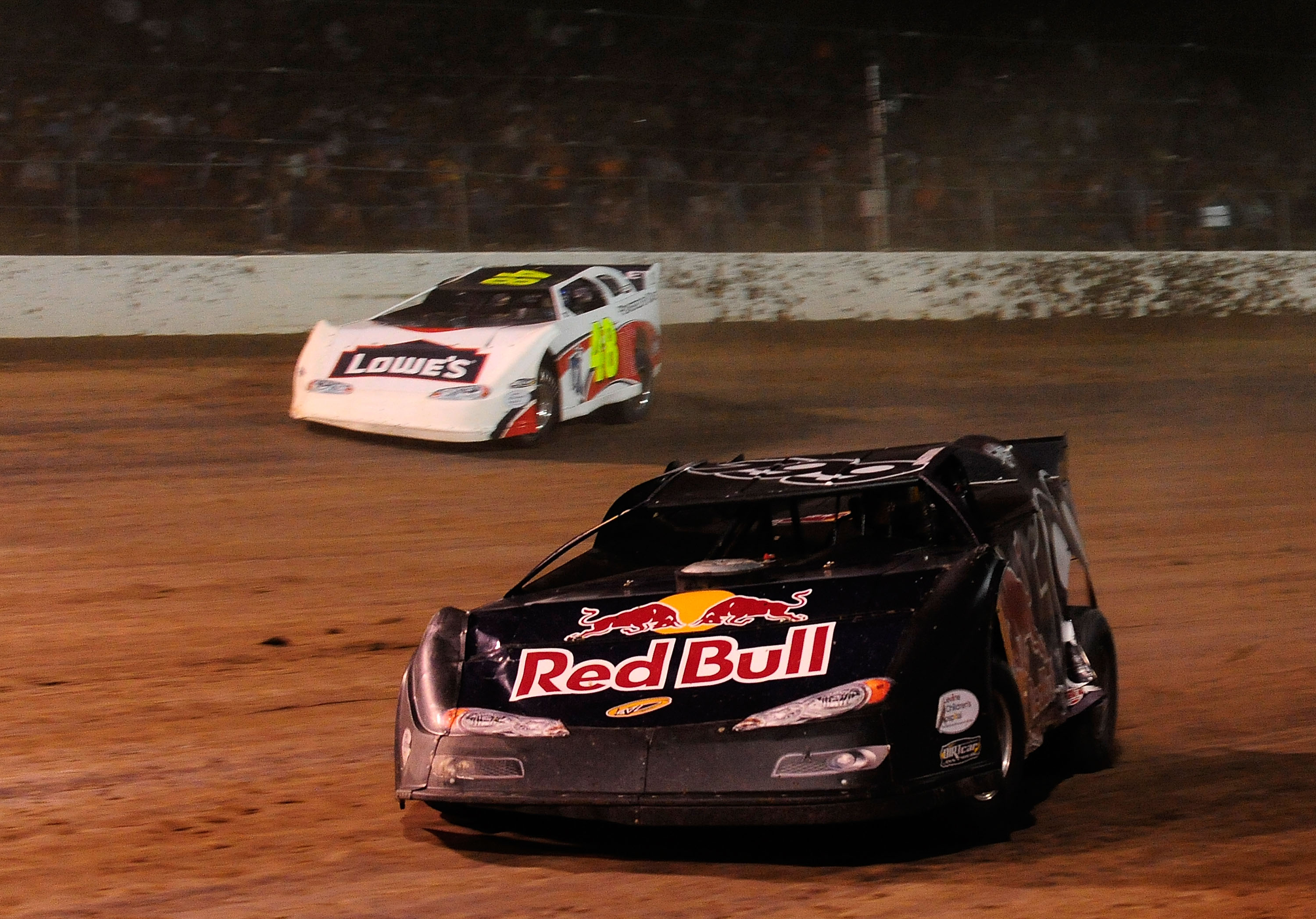 ROSSBURG, OH - JUNE 09:  Travis Pastrana, driver of the #199 Red Bull late model Subaru, leads Jimmie Johnson, driver of the #48 Lowes late model Chevrolet, through turn three during the Gillette Fusion ProGlide Prelude to the Dream at Eldora Speedway on