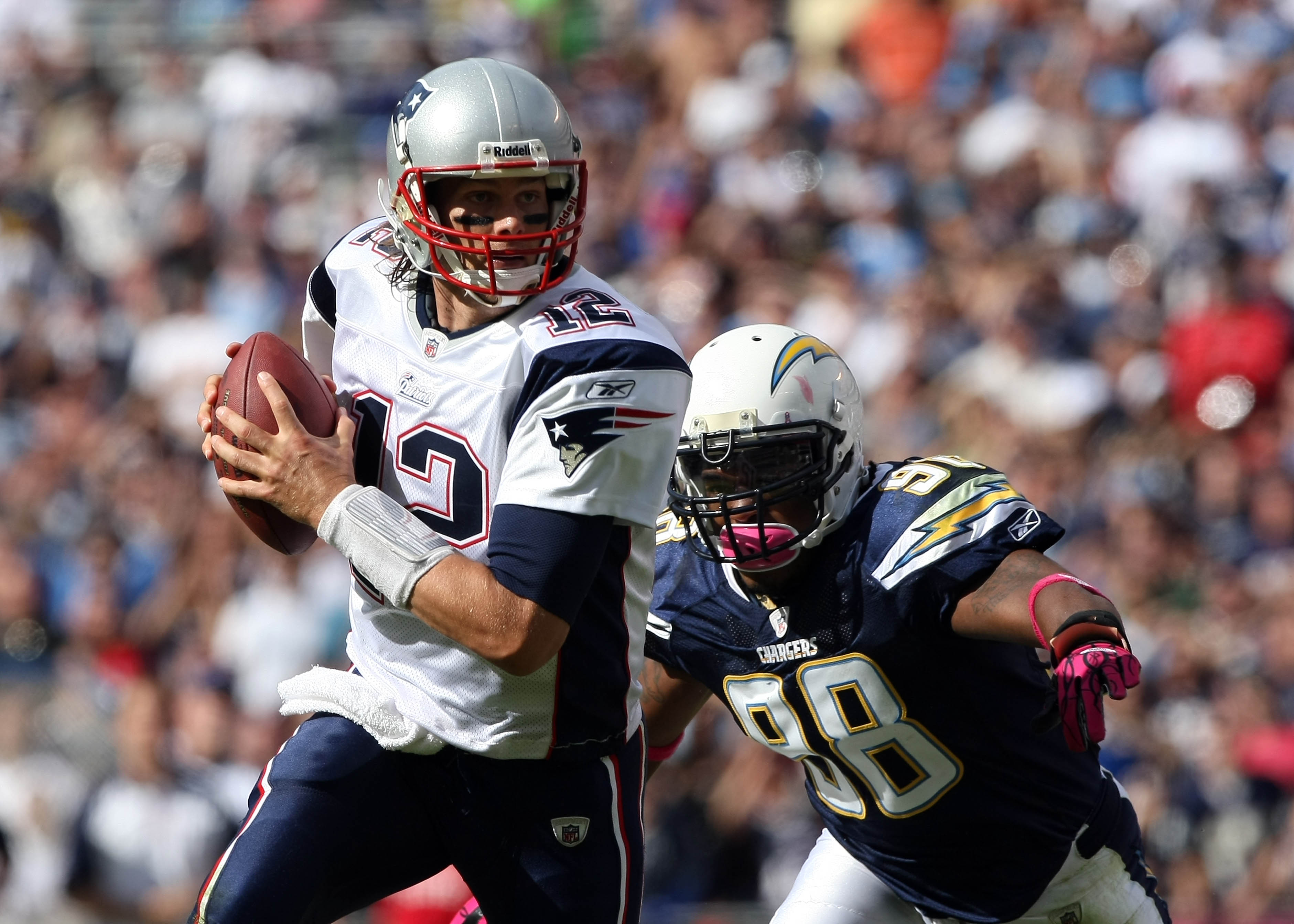 SAN DIEGO - OCTOBER 24:  Quarterback Tom Brady #12 of the New England scrambles with the ball against pressure from the pass rush of Antwan Barnes #98 of the San Diego Chargers during their NFL game on October 24, 2010 at Qualcomm Stadium in San Diego, Ca