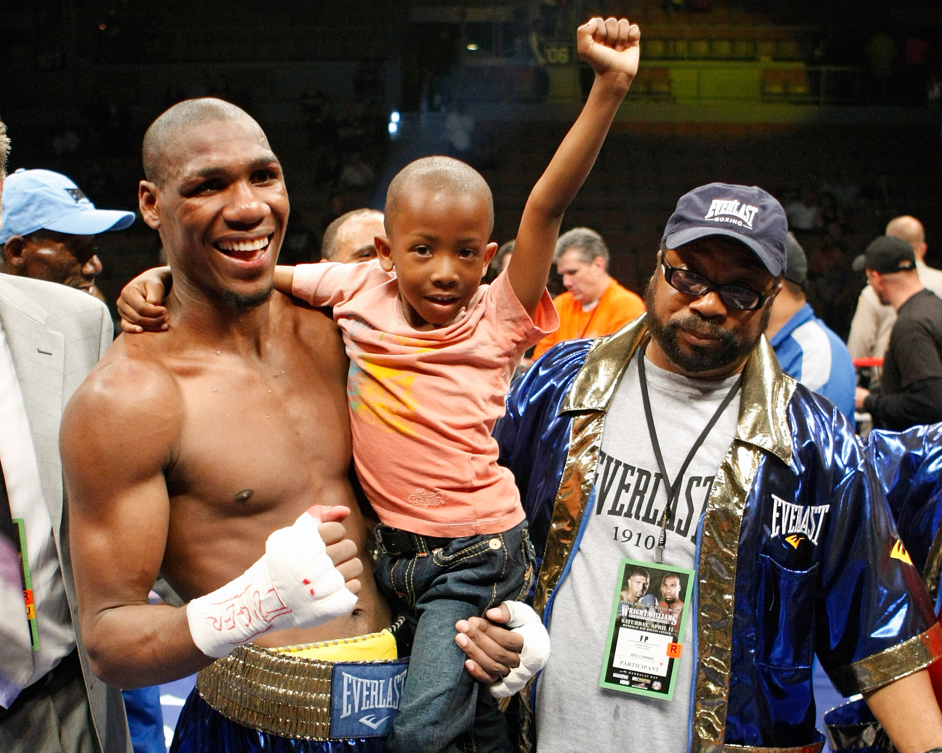LAS VEGAS - APRIL 11:  Paul Williams holds his son Paul Williams Jr. as he and his trainer George Peterson celebrate defeating Winky Wright in a unanimous decision in their middleweight bout at the Mandalay Bay Events Center April 11, 2009 in Las Vegas, N