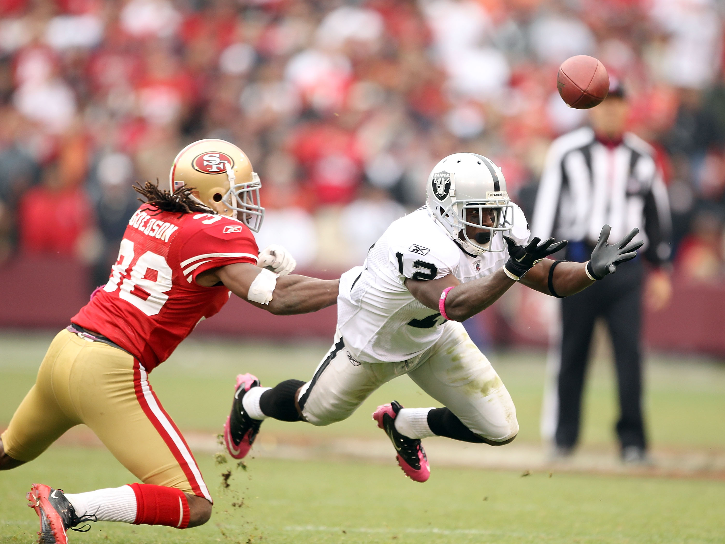 SAN FRANCISCO - OCTOBER 17:  Jacoby Ford #12 of the Oakland Raiders bobbles a ball while defended by Dashon Godson #38 of the San Francisco 49ers at Candlestick Park on October 17, 2010 in San Francisco, California. The ball was intercepted by Takeo Spike
