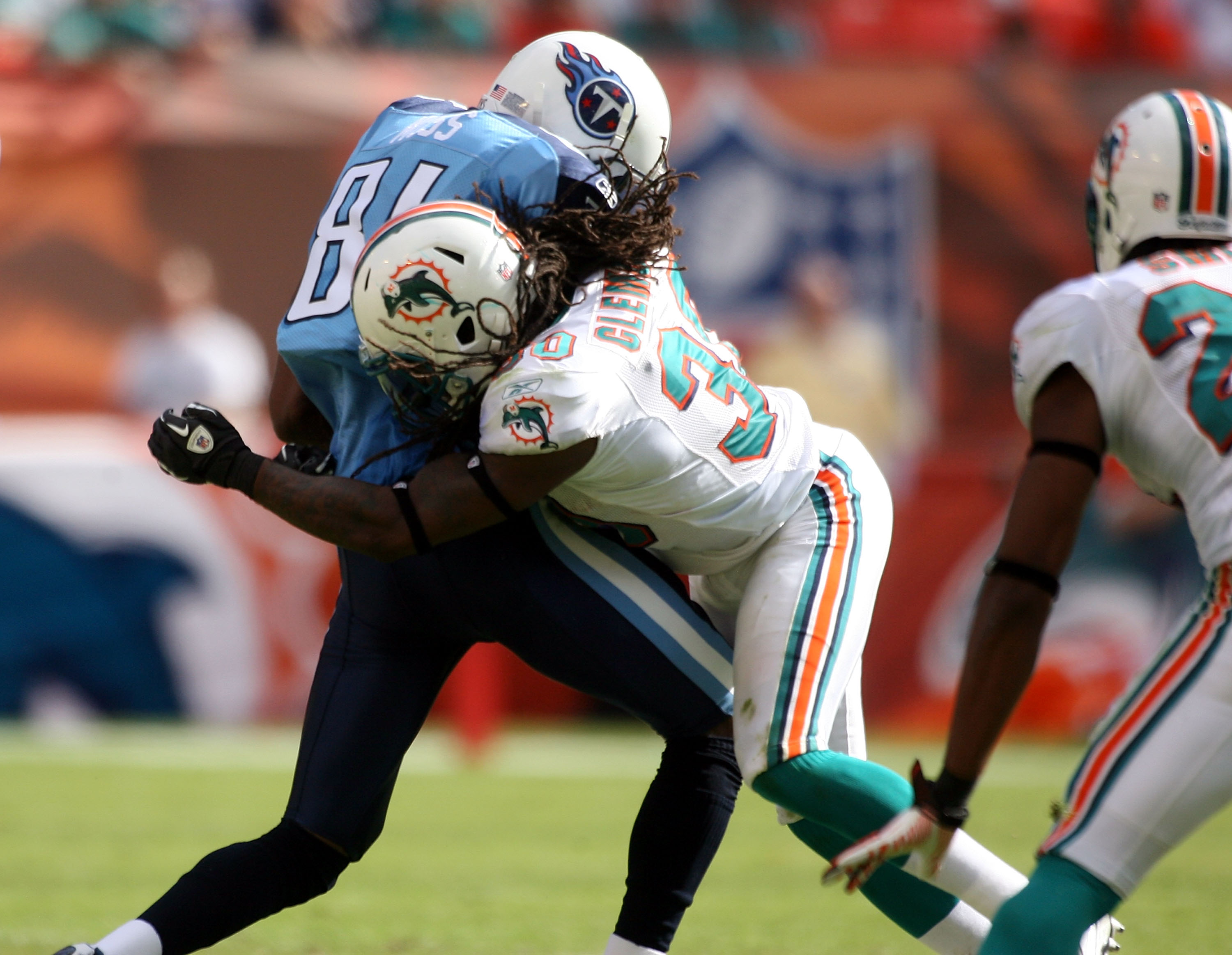 MIAMI - NOVEMBER 14:  Receiver Randy Moss #84 of the Tennessee Titans is hit by Chris Clemons of the Miami Dolphins at Sun Life Stadium on November 14, 2010 in Miami, Florida.  (Photo by Marc Serota/Getty Images)