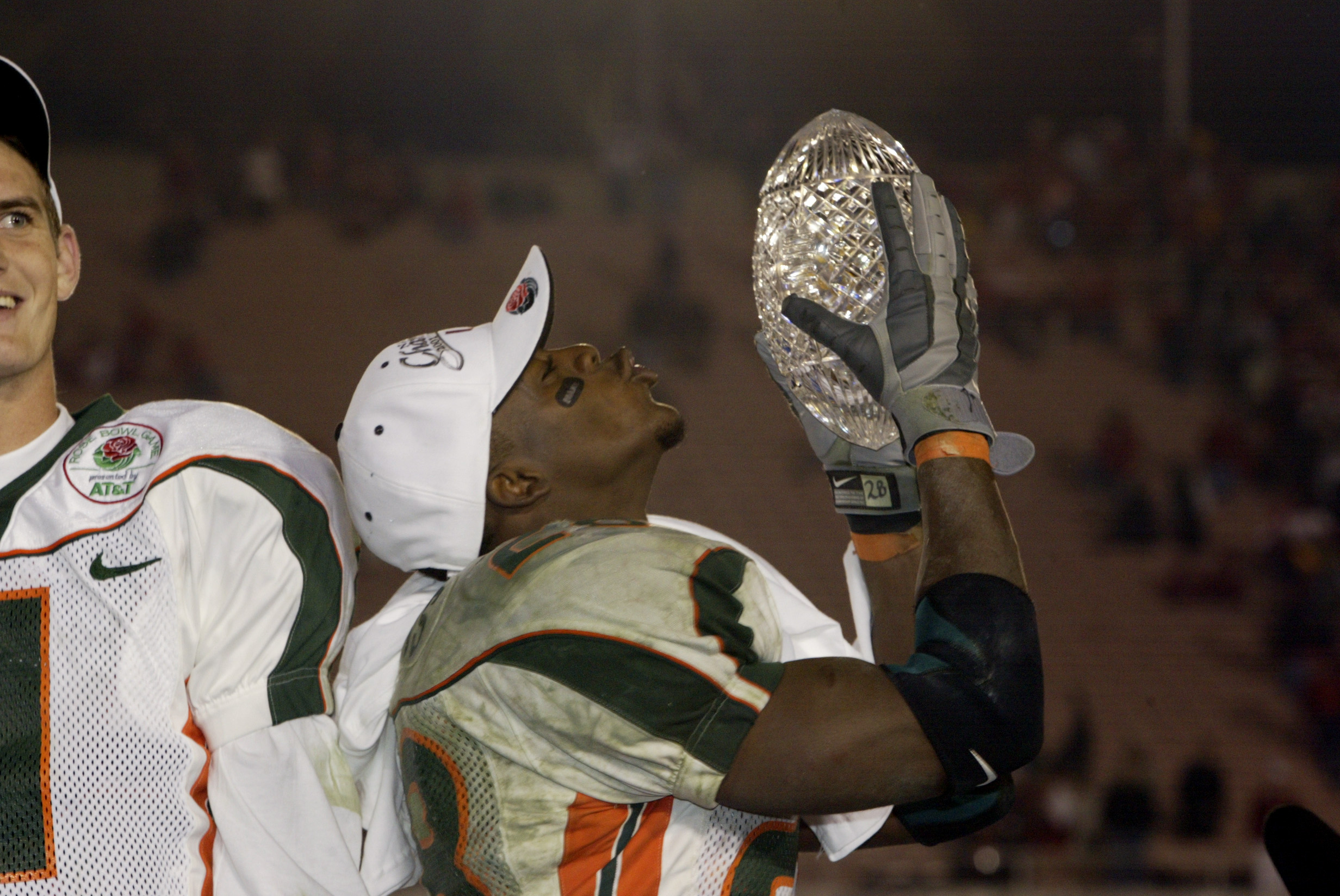 3 Jan 2002:  Clinton Portis #28 of Miami lifts the Sears National Championship trophy as quarterback Ken Dorsey #11 looks on after the win over Nebraska in the Rose Bowl National Championship game at the Rose Bowl in Pasadena, California.  Miami won the g