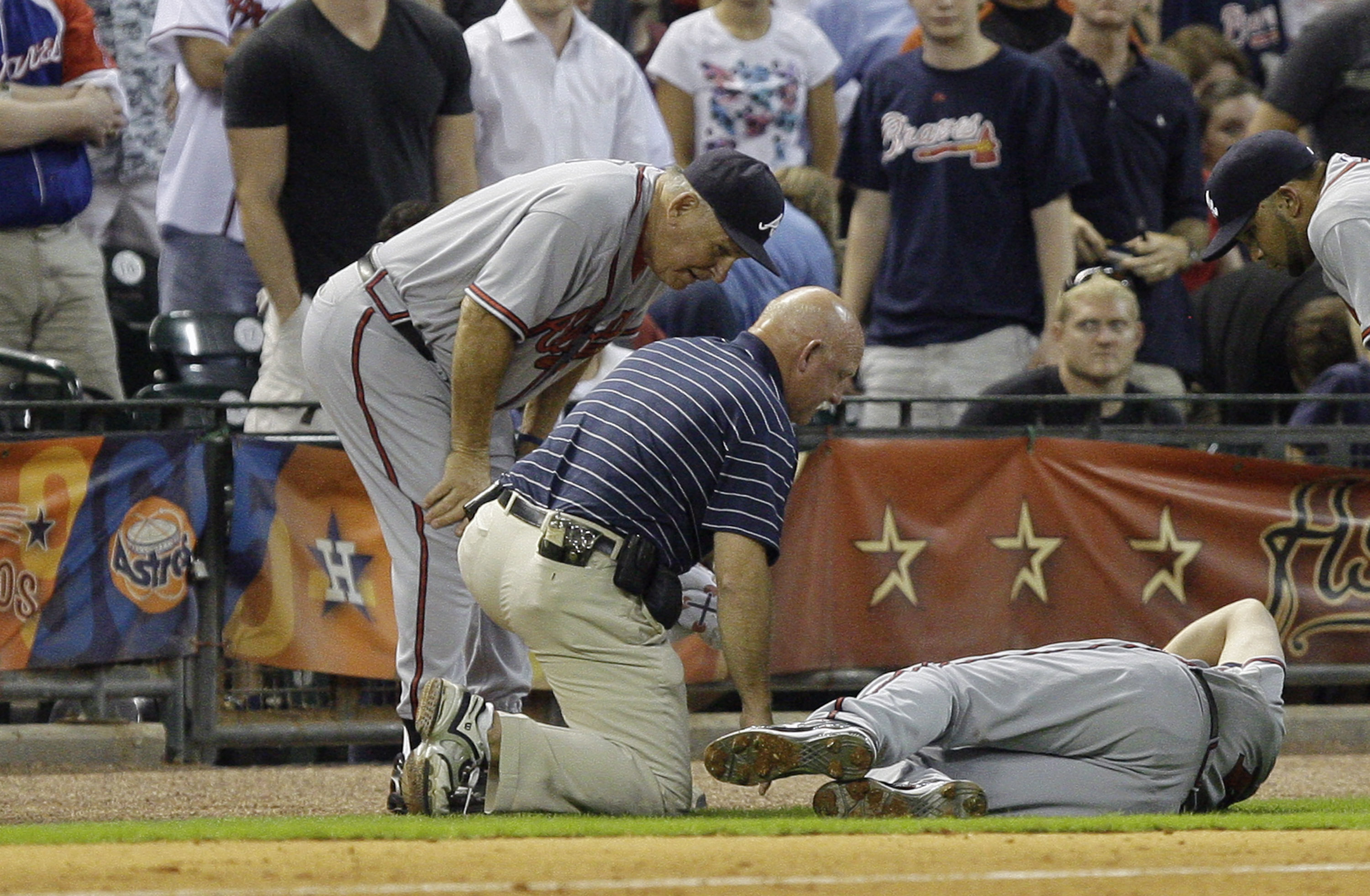 HOUSTON - AUGUST 10:  Third baseman Chipper Jones #10 of the Atlanta Braves is tended to by the trainer and manager Bobby Cox after coming down awkardly behind the base at Minute Maid Park on August 10, 2010 in Houston, Texas. Jones left the game after in