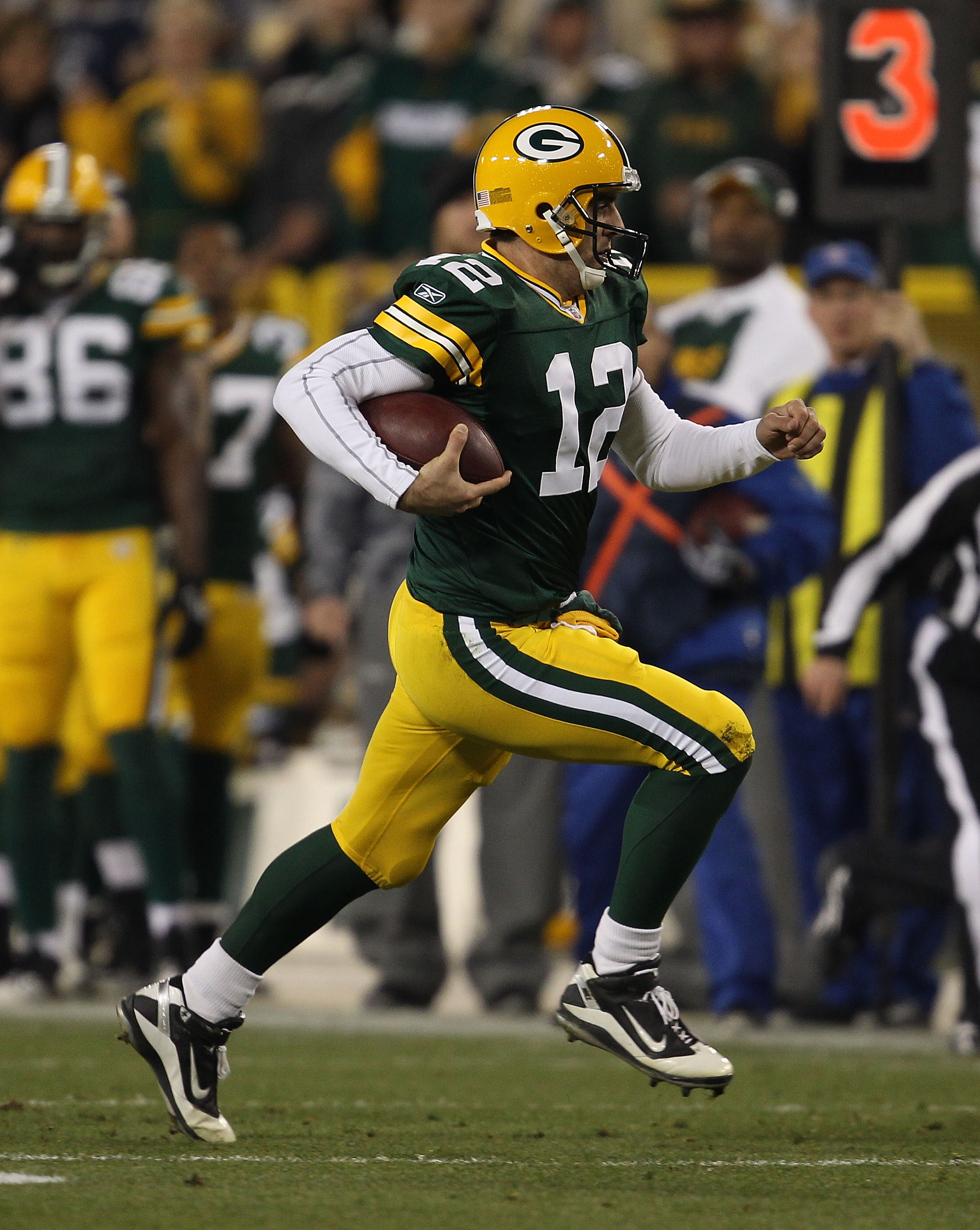 GREEN BAY, WI - NOVEMBER 07: Aaron Rodgers #12 of the Green Bay Packers runs for a first down against the Dallas Cowboys at Lambeau Field on November 7, 2010 in Green Bay, Wisconsin. The Packers defeated the Cowboys 45-7. (Photo by Jonathan Daniel/Getty I