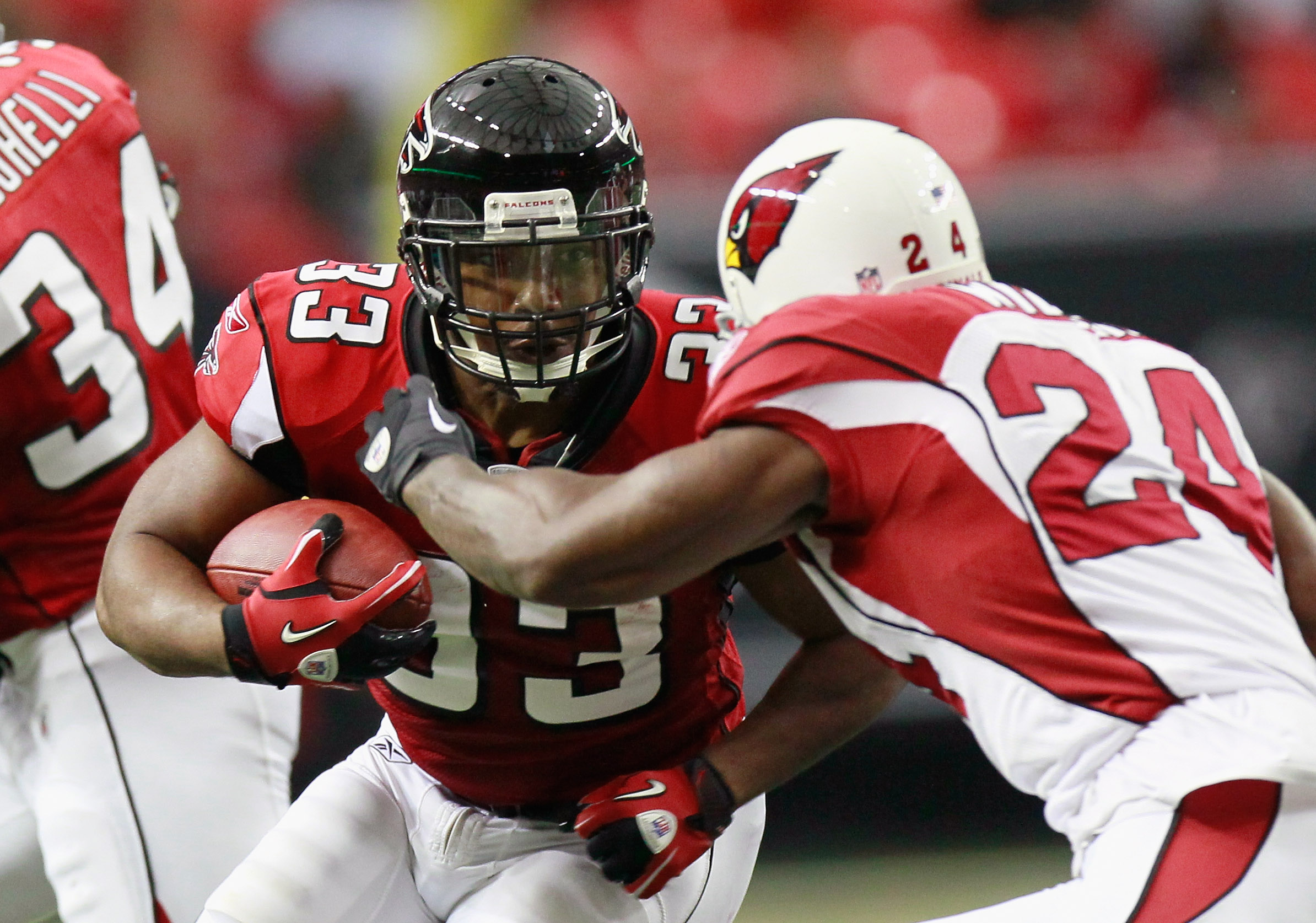 ATLANTA - SEPTEMBER 19:  Michael Turner #33 of the Atlanta Falcons rushes against Adrian Wilson #24 of the Arizona Cardinals at Georgia Dome on September 19, 2010 in Atlanta, Georgia.  (Photo by Kevin C. Cox/Getty Images)