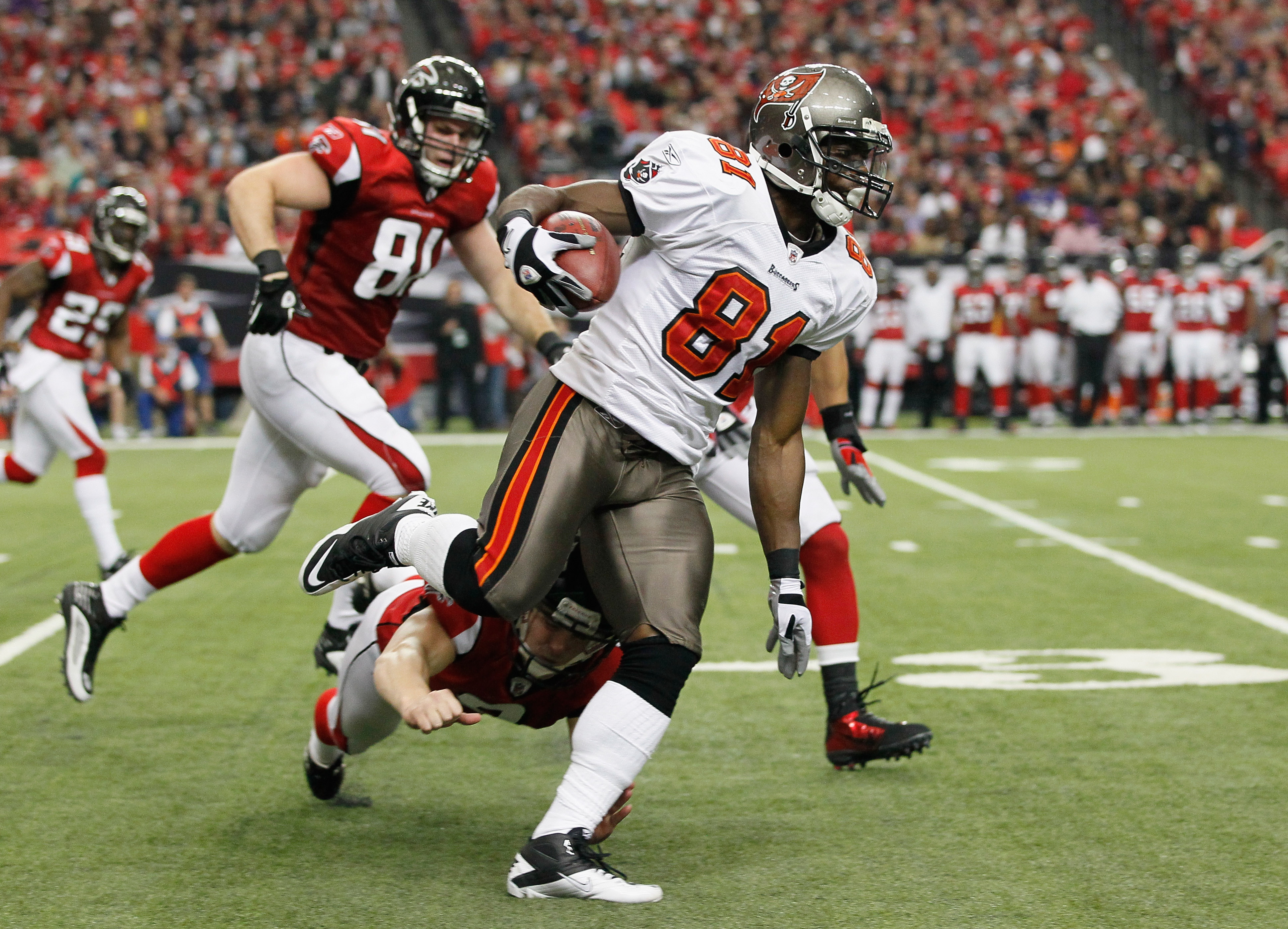 ATLANTA - NOVEMBER 07:  Micheal Spurlock #81 of the Tampa Bay Buccaneers returns a punt and avoids a tackle by Michael Koenen #9 of the Atlanta Falcons for a touchdown at Georgia Dome on November 7, 2010 in Atlanta, Georgia.  (Photo by Kevin C. Cox/Getty