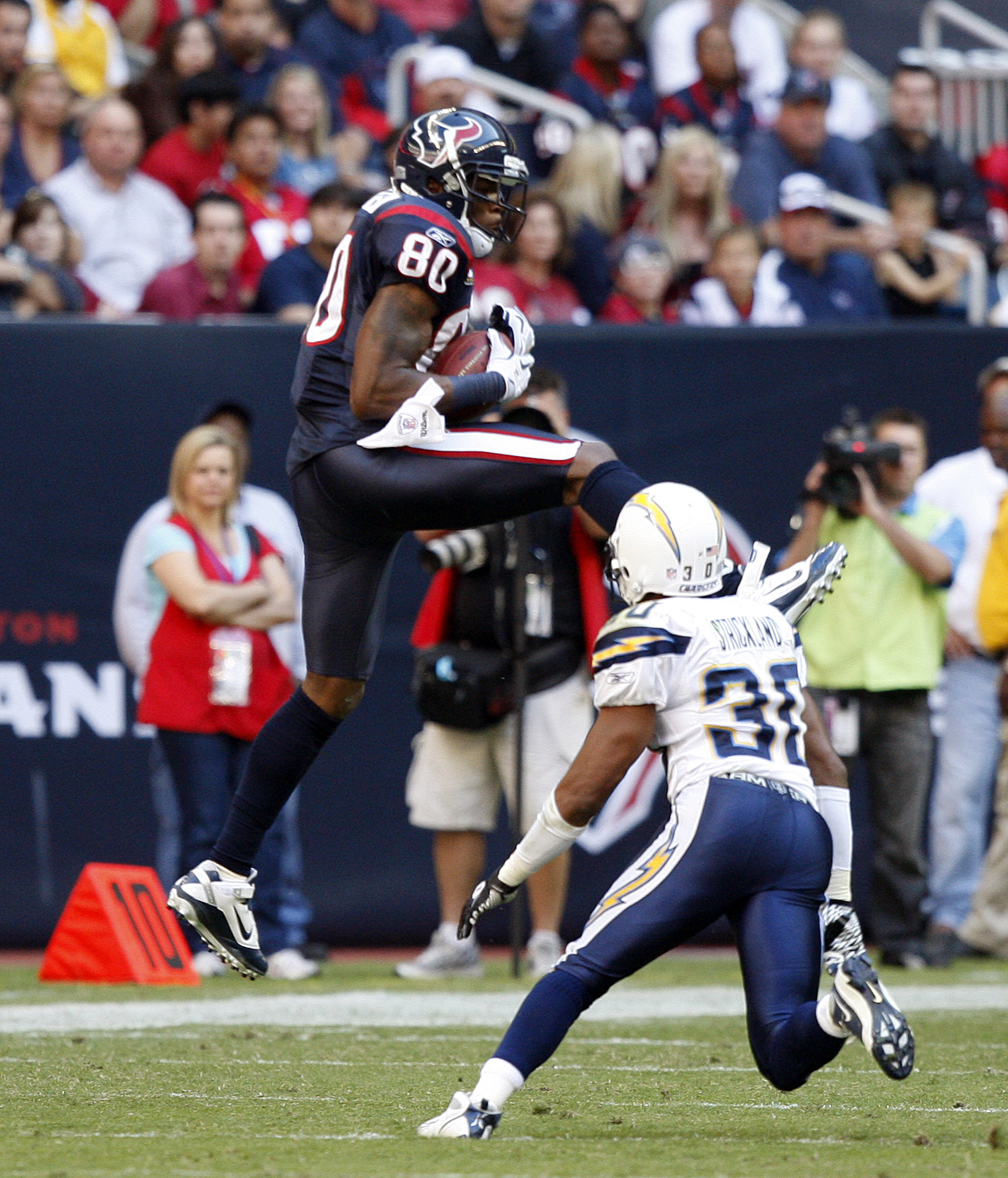 HOUSTON - NOVEMBER 07:  Wide receiver Andre Johnson #80 of the Houston Texans completes a pass in front of  cornerback Donald Strickland #30 of the San Diego Chargers at Reliant Stadium on November 7, 2010 in Houston, Texas.  (Photo by Bob Levey/Getty Ima