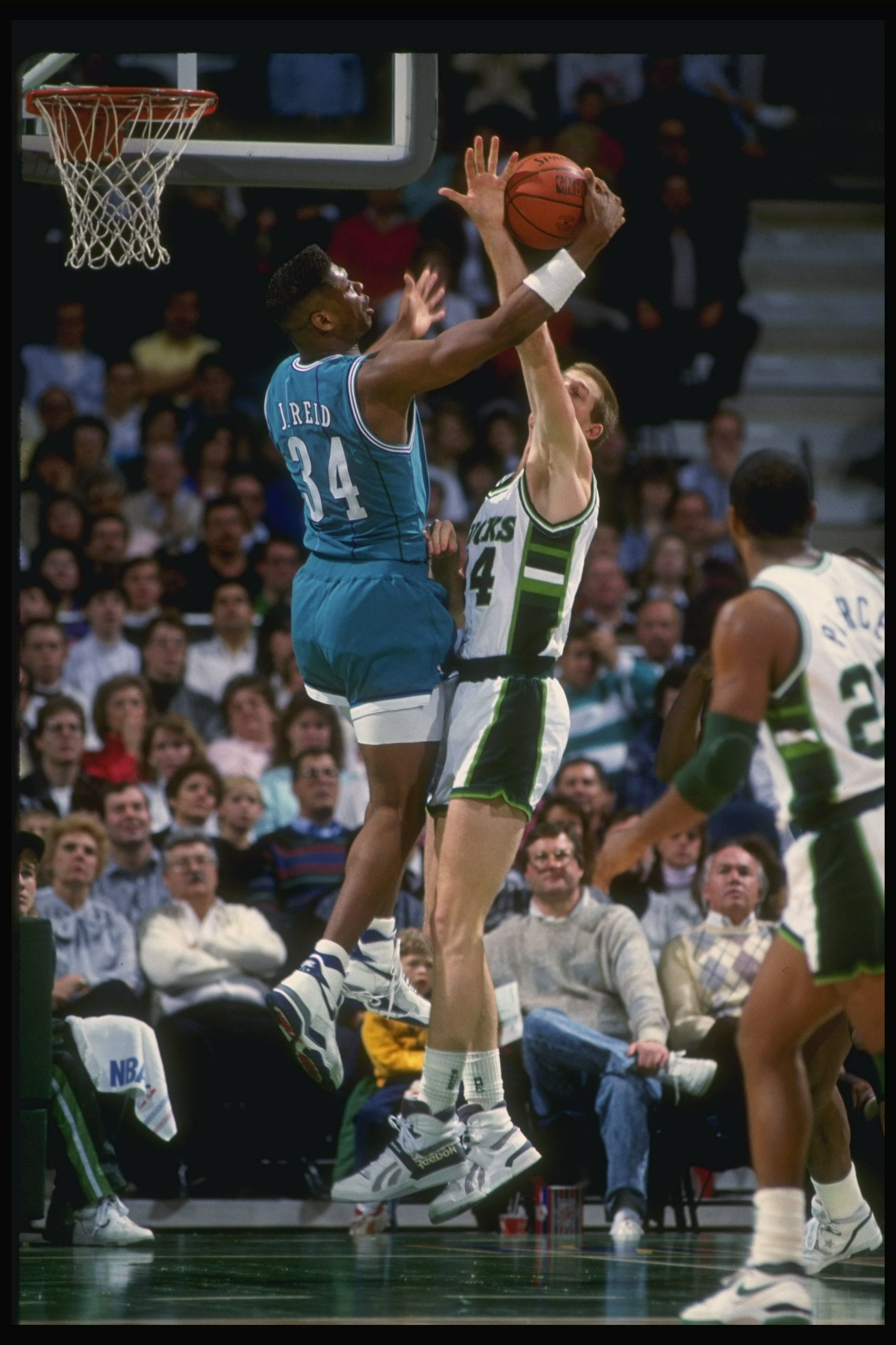 1989-1990:  Forward J. R. Reid of the Charlotte Hornets (left) battles for the ball with center Brad Lohaus of the Milwaukee Bucks during a game at the Bradley Center in Milwaukee, Wisconsin. Mandatory Credit: Allsport  /Allsport