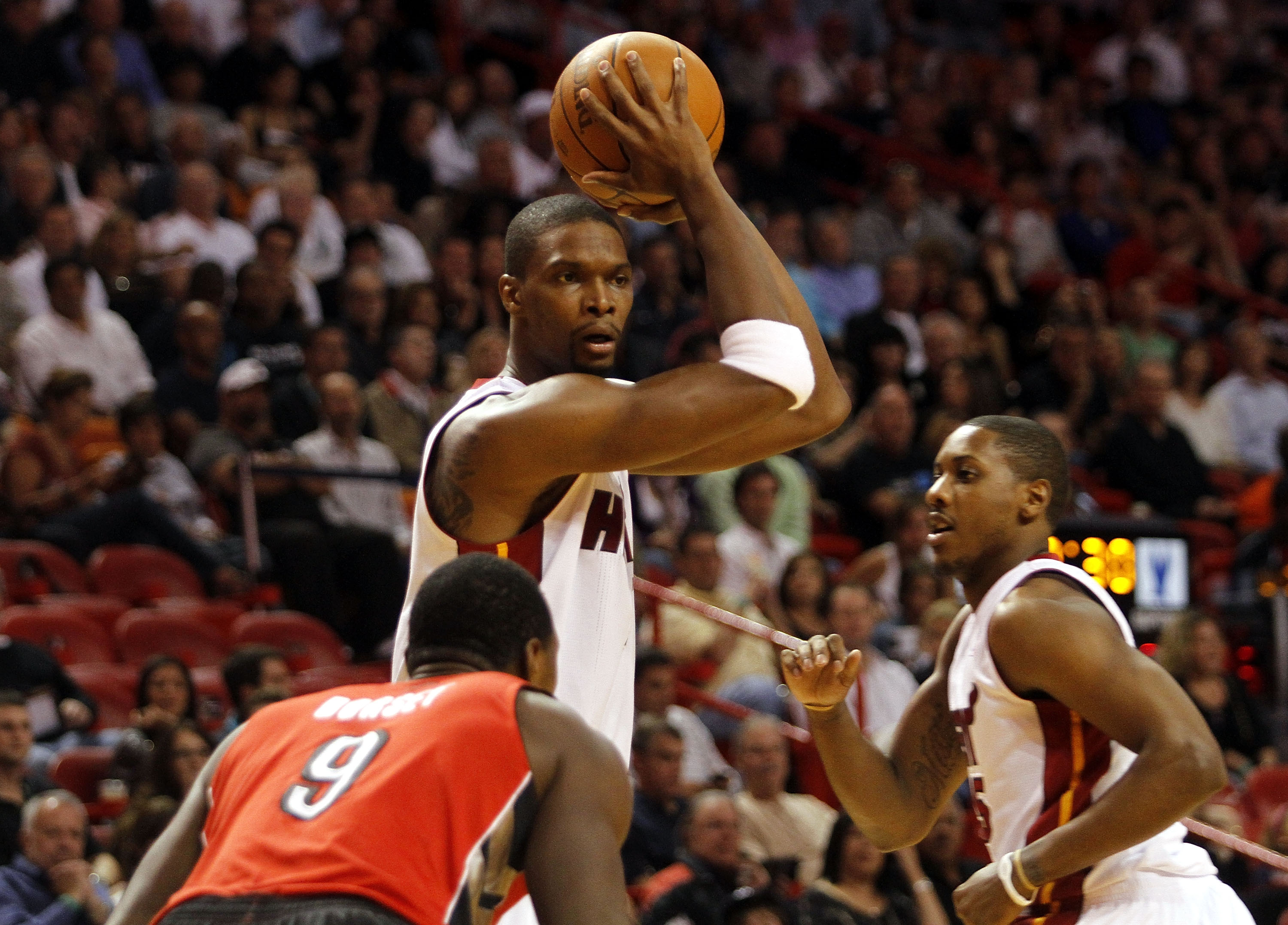 MIAMI - NOVEMBER 13:  Forward Chris Bosh #1 of the Miami Heat drives against Joey Dorsey #9 of the Toronto Raptors at American Airlines Arena on November 13, 2010 in Miami, Florida. NOTE TO USER: User expressly acknowledges and agrees that, by downloading