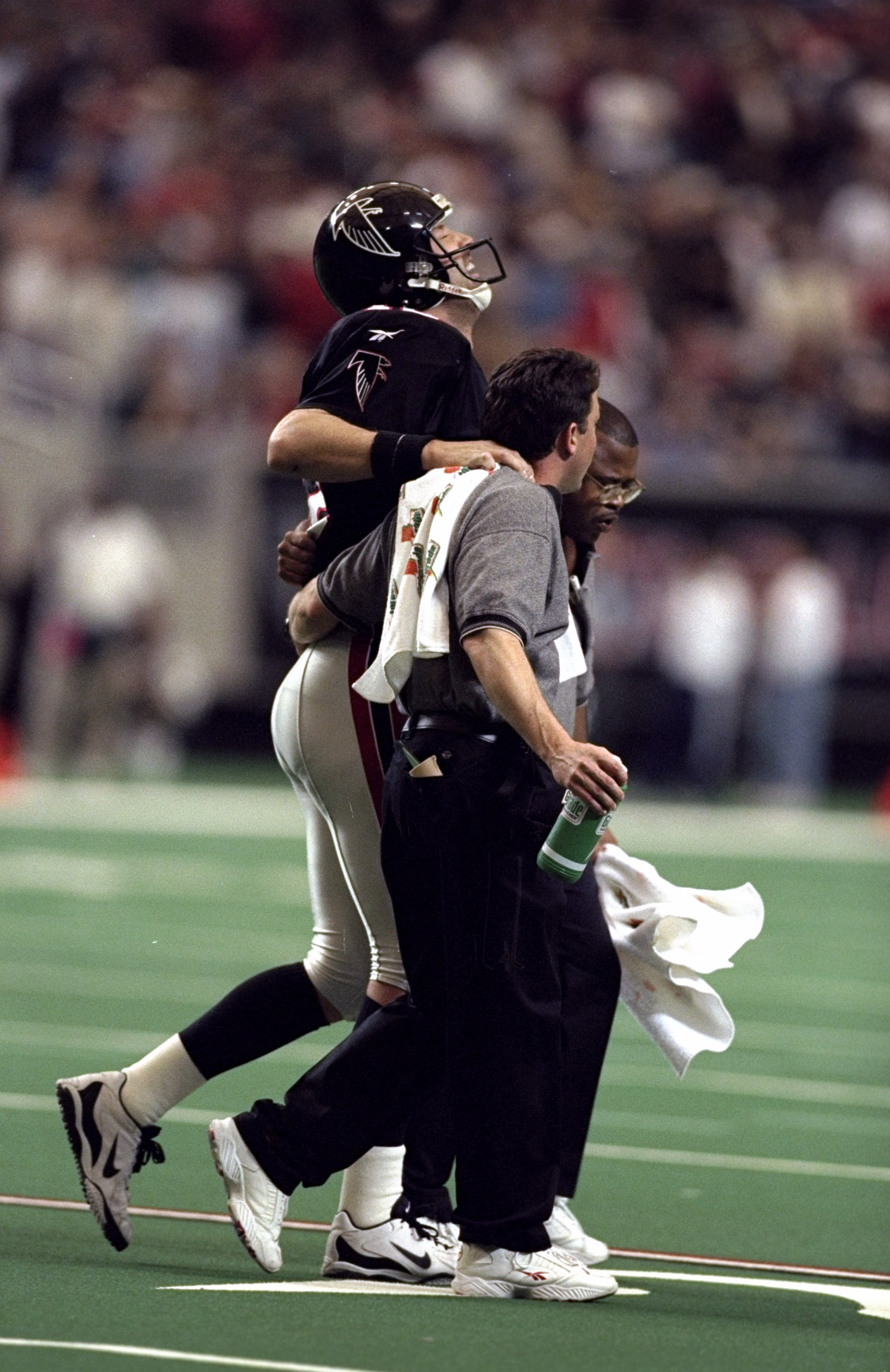 27 Dec 1998: Chris Chandler #12 of the Atlanta Falcons is helped off the field during the game against the Miami Dolphins at the Georgia Dome in Atlanta, Georgia. The Falcons defeated the Dolphins 38-16.