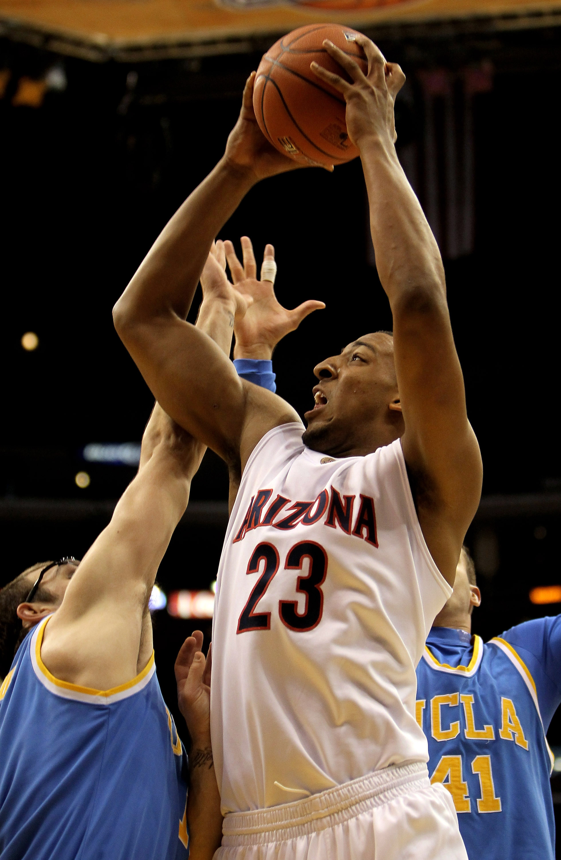LOS ANGELES - MARCH 11:   Derrick Williams #23 of the Arizona Wildcats shoots over Reeves Nelson #11 of the UCLA Bruins during the quarterfinals of the Pac-10 Basketball Tournament at Staples Center on March 11, 2010 in Los Angeles, California.  (Photo by
