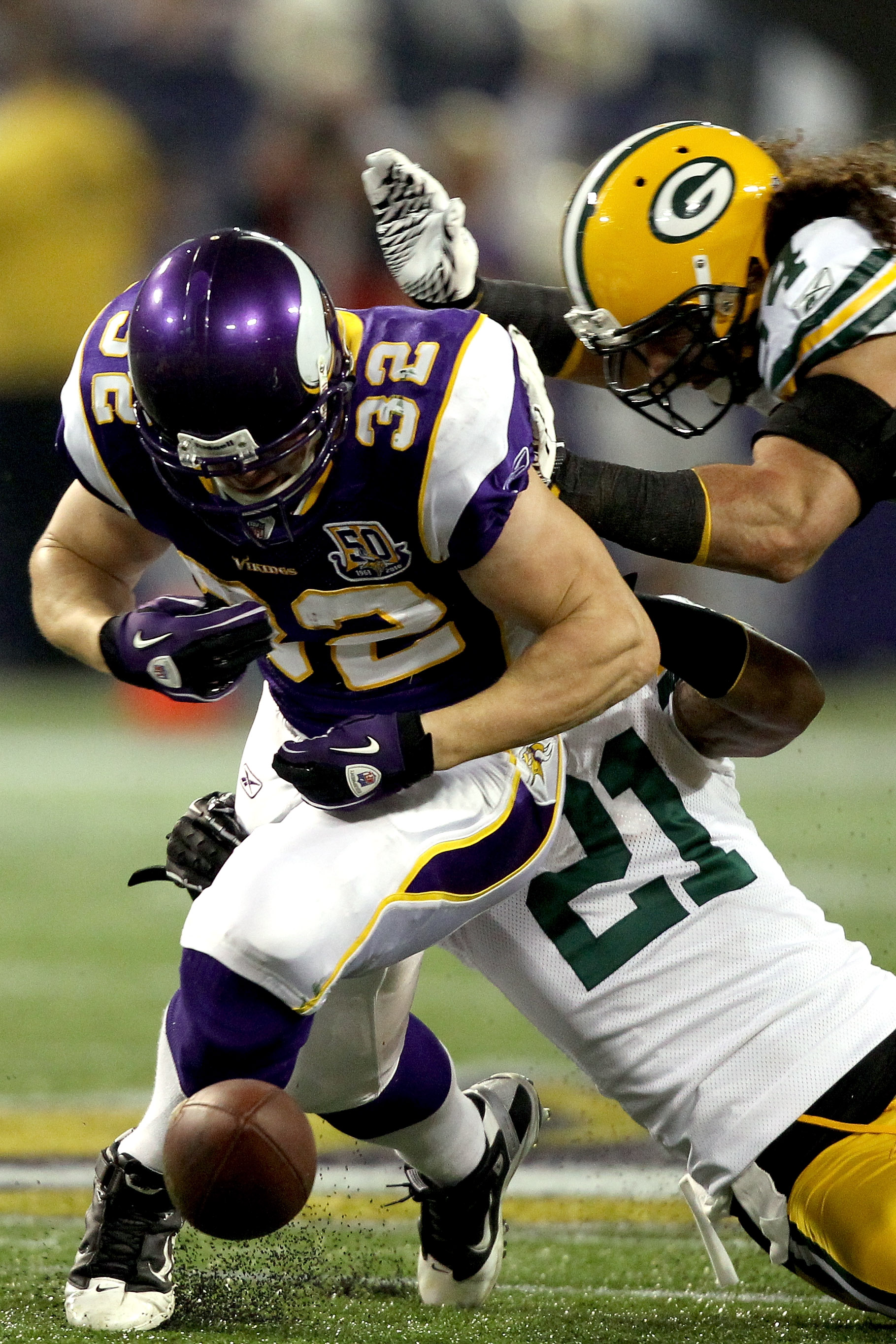 MINNEAPOLIS - NOVEMBER 21:  Toby Gerhart #32 of the Minnesota Vikings has the ball jarred loose by Charles Woodson #21 and Brandon Chillar #54 of the Green Bay Packers at the Hubert H. Humphrey Metrodome on November 21, 2010 in Minneapolis, Minnesota.  (P